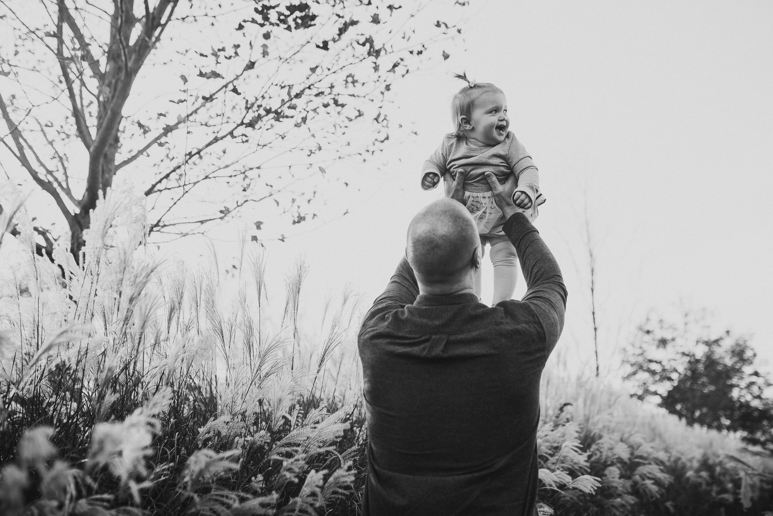 black and white father daughter throw lift Lifestyle Documentary Fall Autumn Sunset Golden Hour Family toddler first birthday cake smash Beaverdam Run Broadlands Loudoun Virginia Marti Austin Photography