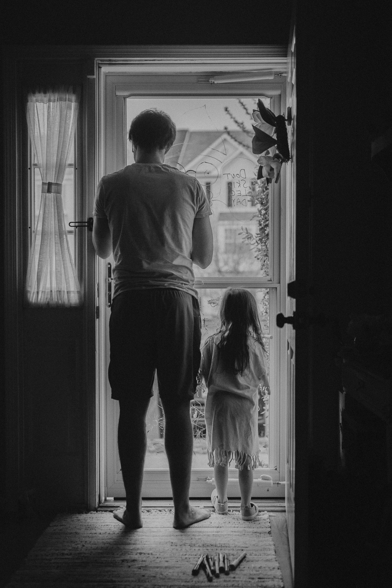 black and white father daughter glass door drawing lifestyle documentary family childhood Ashburn Loudoun Northern Virginia Marti Austin Photography