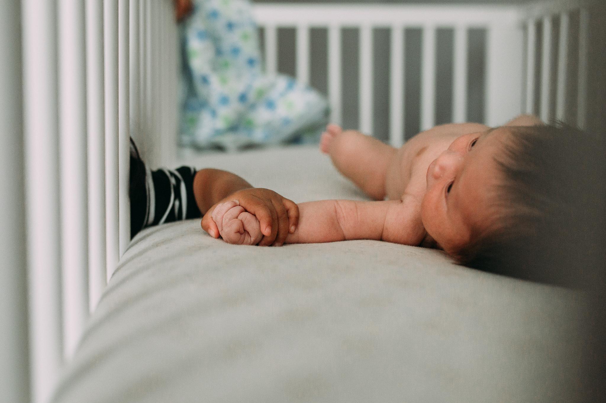 big sister baby boy brother holding hands crib lifestyle documentary newborn family Aldie Loudoun Virginia Marti Austin Photography
