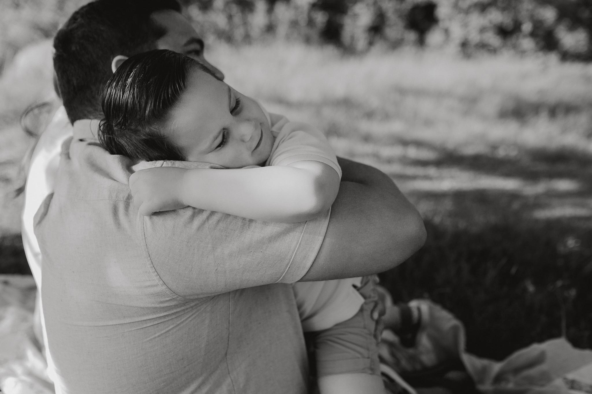 black and white father son hug  Brambleton Beaverdam Reservoir Loudoun Virginia Lifestyle Documentary Family Marti Austin Photography