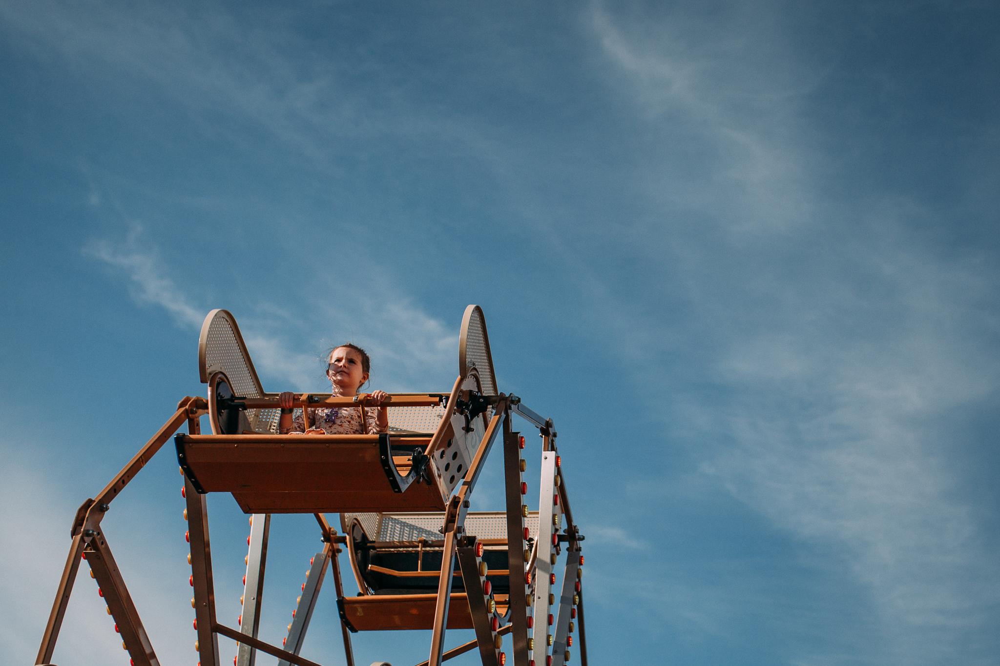Blue sky girl on ferris wheel carnival summer Ashburn Loudoun Northern Virginia family lifestyle documentary childhood Marti Austin Photography