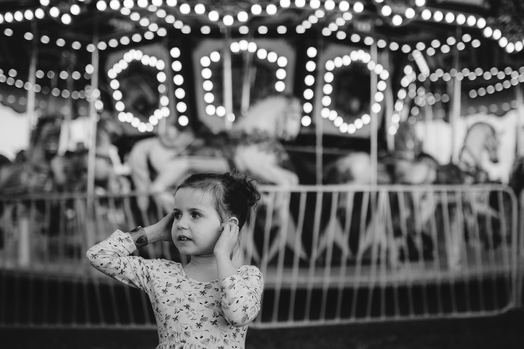 Black and white girl carnival merry go round carousel lights bokeh summer Ashburn Loudoun Northern Virginia family lifestyle documentary childhood Marti Austin Photography