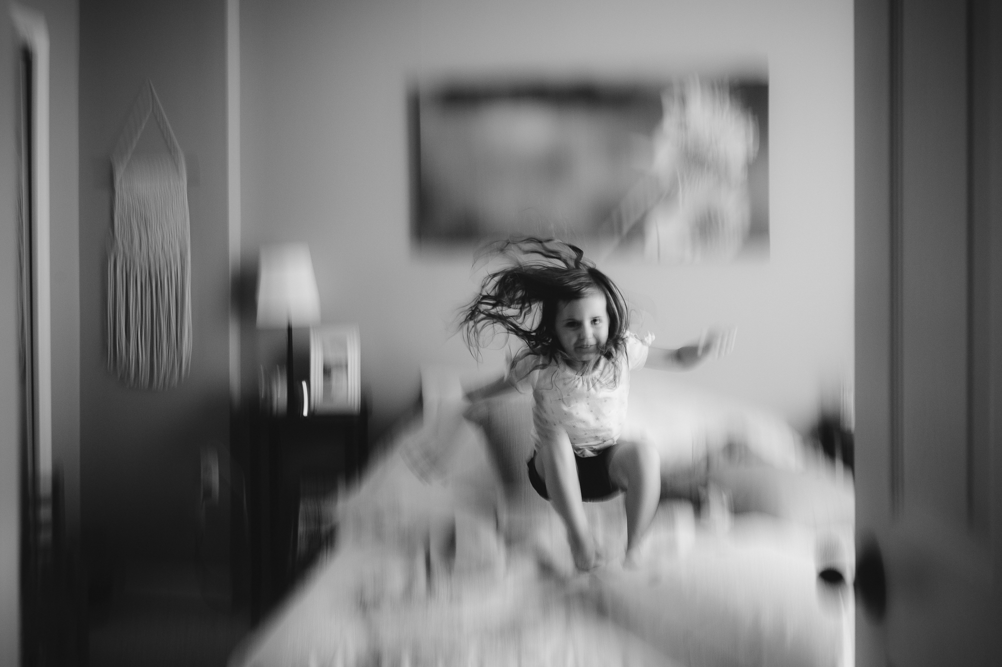 black and white girl jumping on bed panning movement motion summer Ashburn Loudoun Northern Virginia family lifestyle documentary childhood Marti Austin Photography