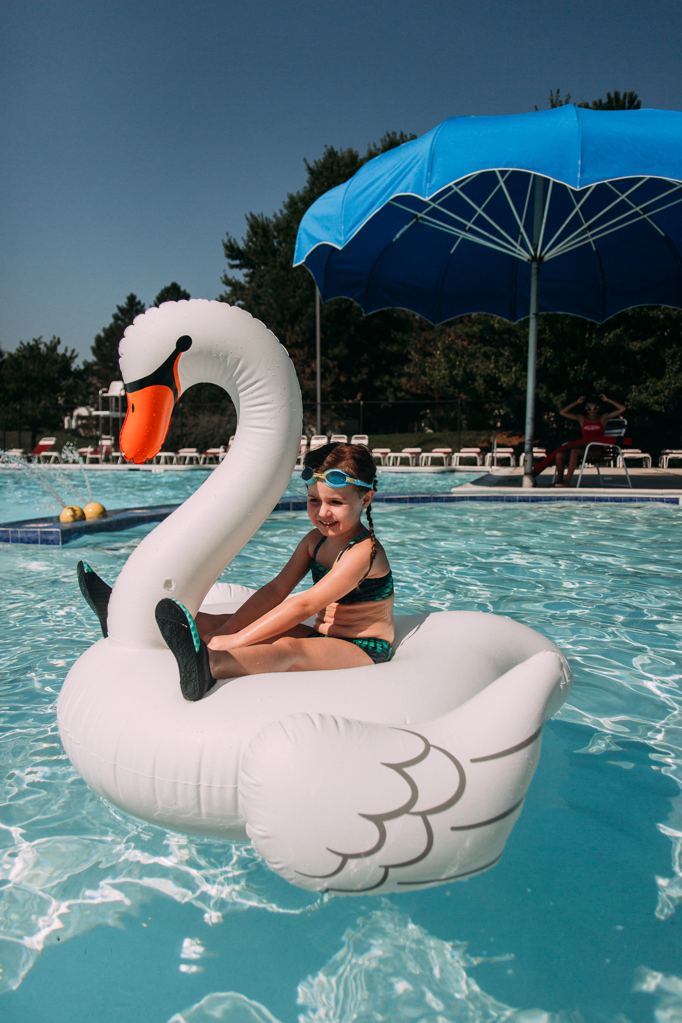 girl  floating on giant swan at swimming pool summer Ashburn Loudoun Northern Virginia family lifestyle documentary childhood Marti Austin Photography