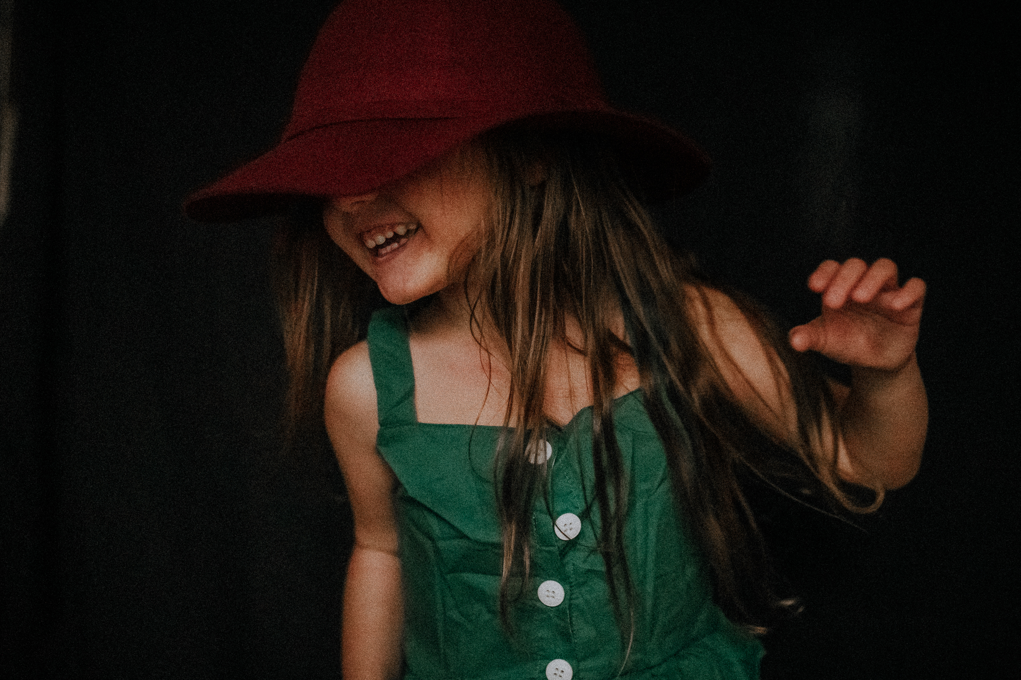 girl dancing and laughing in red hat