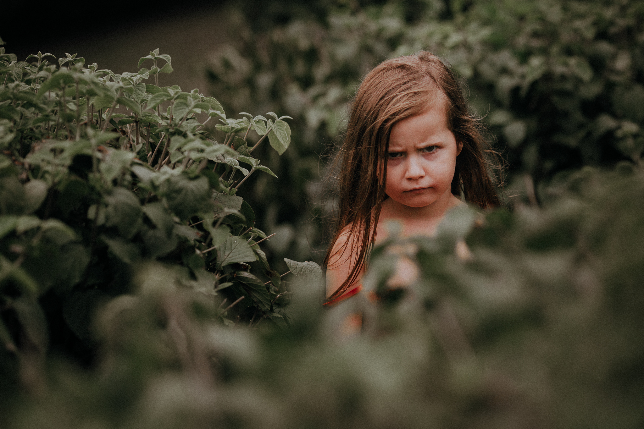 girl scowling at camera from bushes summer Ashburn Loudoun Northern Virginia family lifestyle documentary childhood Marti Austin Photography