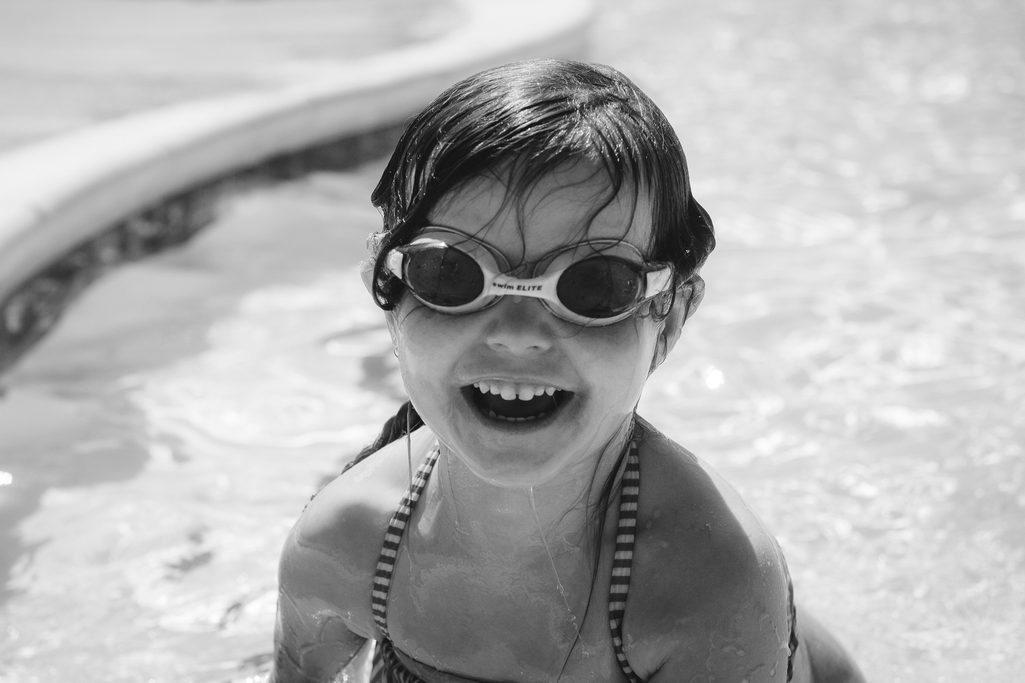 black and white portrait girl smiling and laughing at pool summer Ashburn Loudoun Northern Virginia family lifestyle documentary childhood Marti Austin Photography