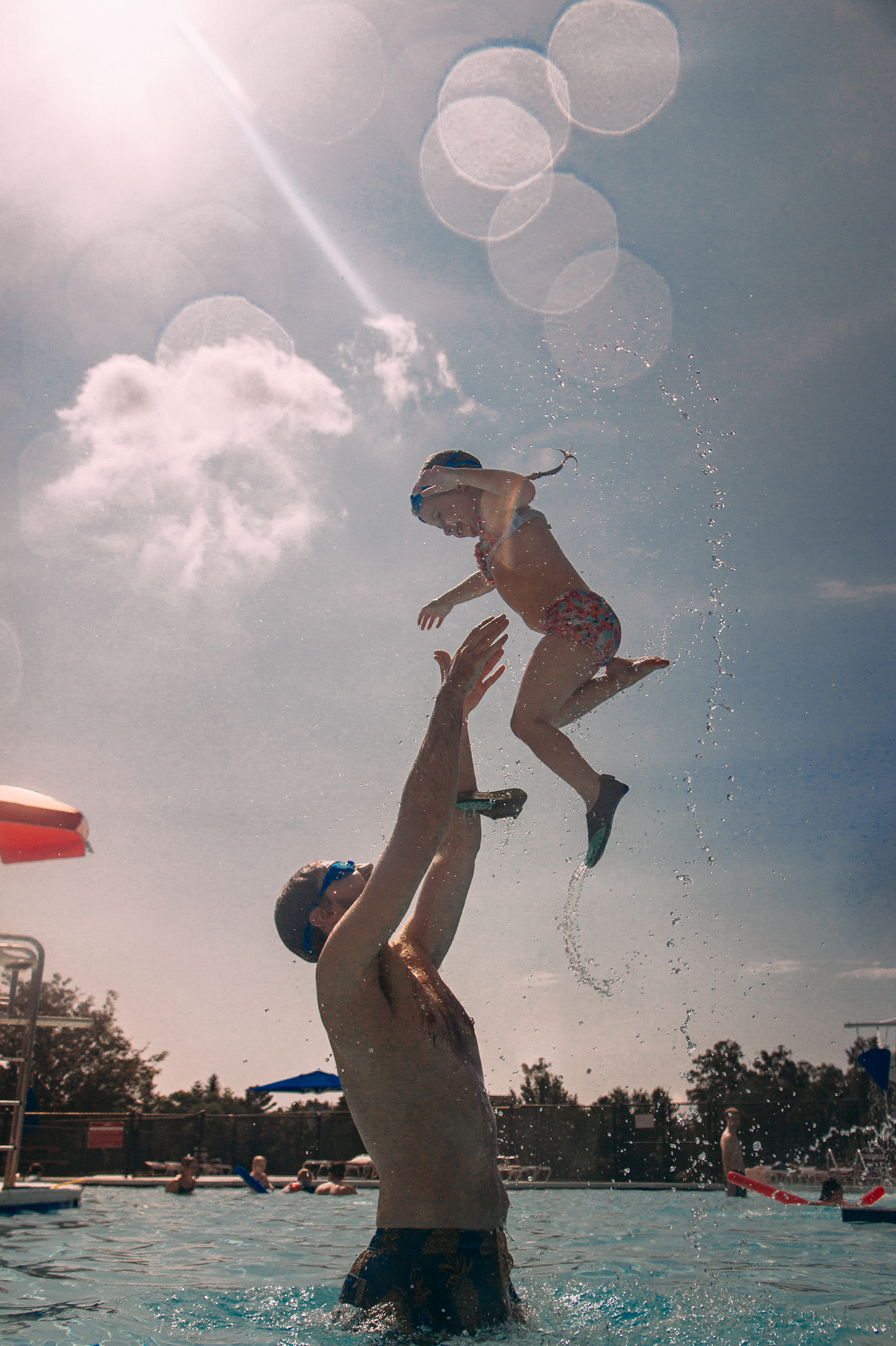 father tossing daughter into air at pool summer Ashburn Loudoun Northern Virginia family lifestyle documentary childhood Marti Austin Photography
