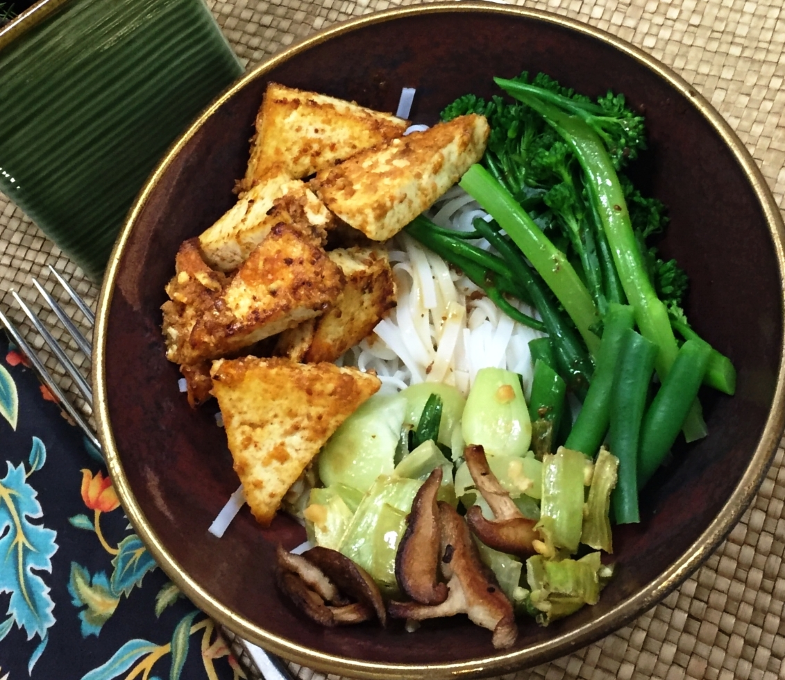 - Yields 2 Serves2 portions rice noodles200 gm. firm tofu1 bunch broccolini100 gm. or 12 green beans2 small bunches of bok choy6 shiitake mushrooms2 tsp. lime juice2 Tbsp. white miso paste2 Tbsp. Mirin1 1/2 Tbsp. tamari sauce /or low salt soy sauce1 tsp. grated ginger1 clove of crushed1 tsp. coriander powder½ tsp. turmeric1 Tbsp. sesame oilBlack pepper to taste2 Tbsp. Oil2 spring onions snipped on a slant for a garnish.Cook rice noodles according to package instructions and keep aside.Drain tofu and wrap in a paper towel until dry. Cut into wedges.Mix together all the sauces with the ginger and garlic.Dredge the wedges of tofu with the coriander and turmeric powder and some oil, salt and pepper. Pour a little oil into a frying pan and brown the tofu on both sides about 3 minutes each side and allow to rest. Cook the shiitake mushrooms with a tsp. of tamari sauce and oil. Set aside.Steam the broccolini and beans for 3-4 minutes. Run under cold water to keep the colour. Lightly sauté the bokchoy. Now your bowl is ready to be assembled.Warm the rice noodles by pouring some boiling water. Drain and place in the bowl, drizzle a bit of the sauce on the noodles, arrange the tofu, vegetables, a bit more sauce and garnish with spring onions.