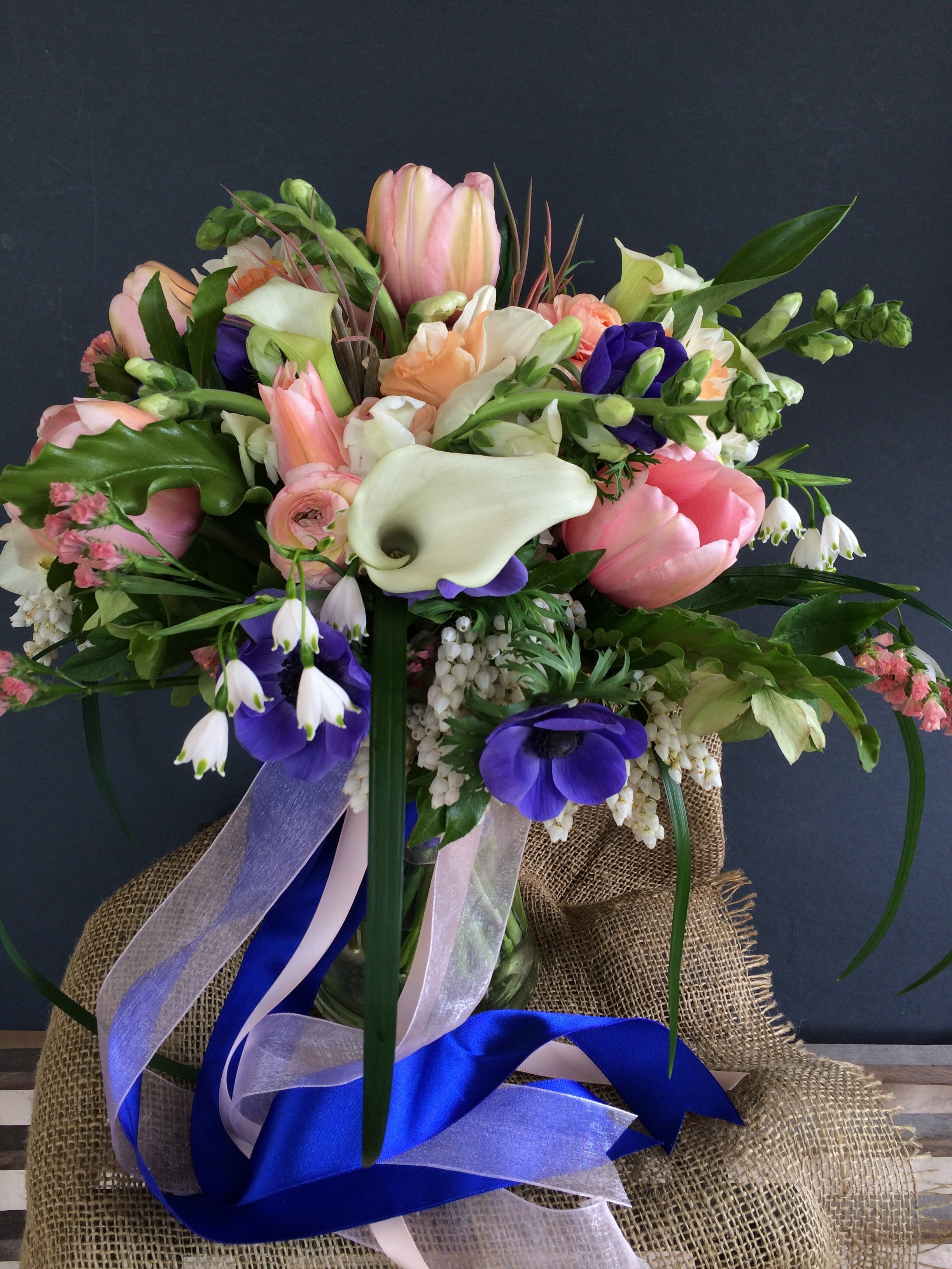An early spring bridal bouquet of french tulips, peony, anemone, calla lilies and snow drops
