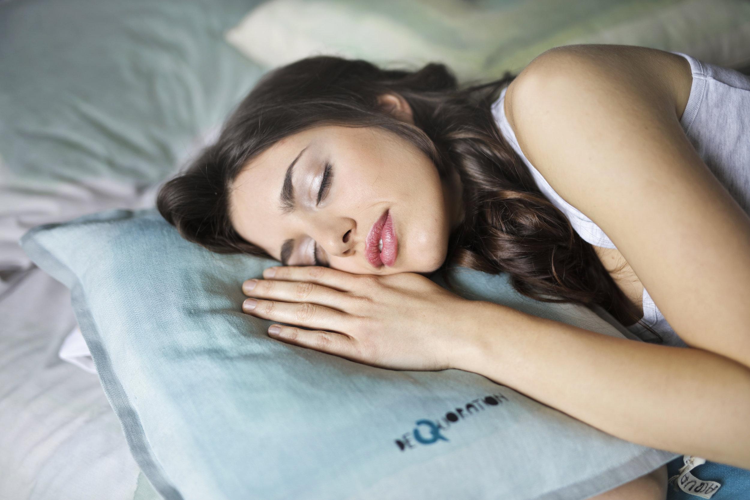 kvinder-sover-med-hovedet-på-en-pude