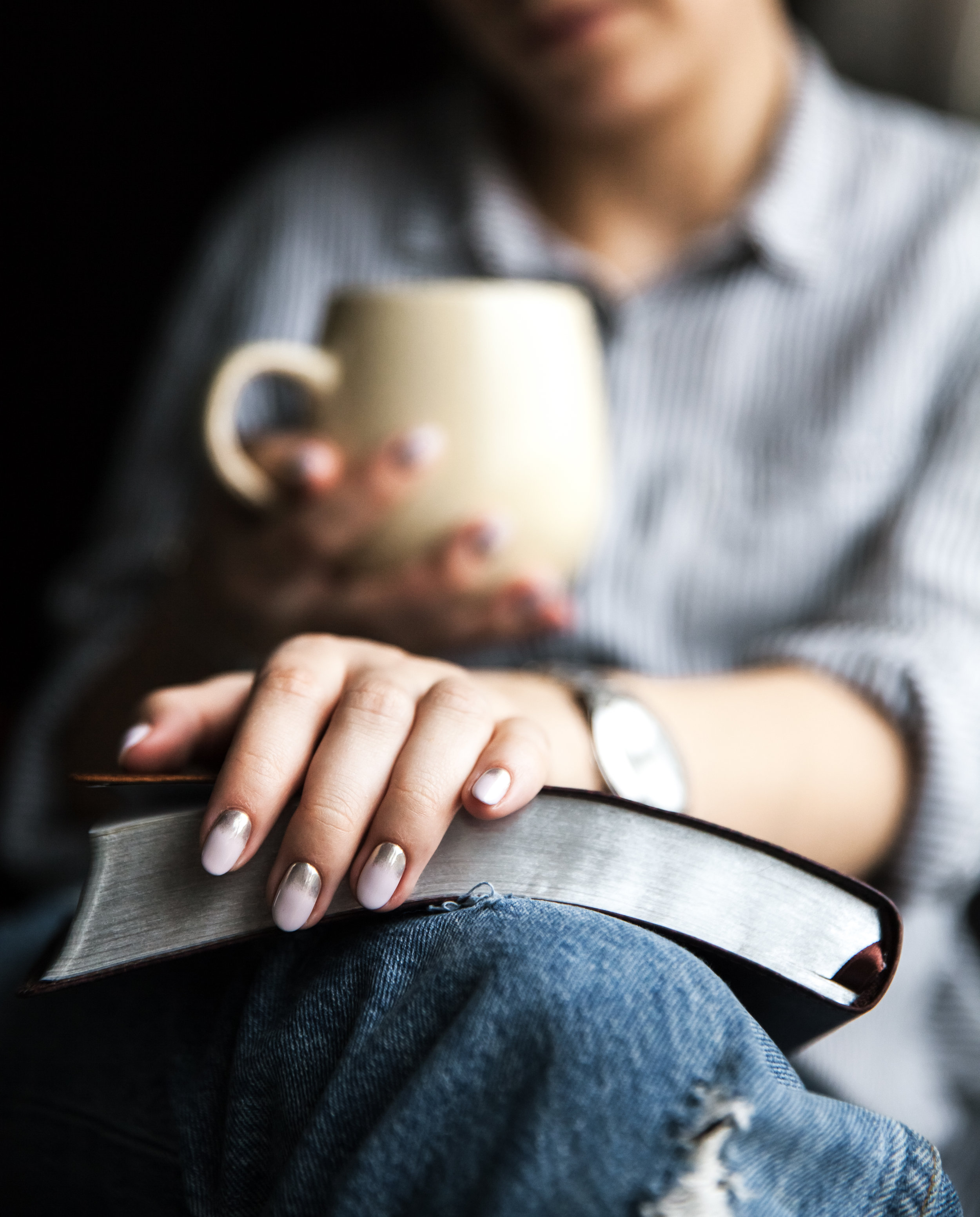 young-woman-reading-a-book-and-holding-cup-of-tea-UF5W6MA.jpg