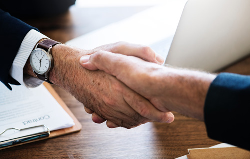 Chiropracter shaking hands with client over desk