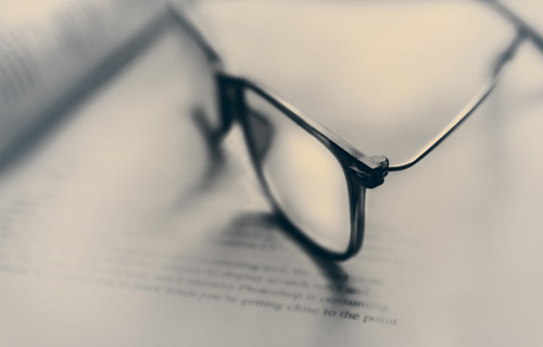 Doctor's glasses resting on medical textbook