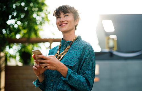 Happy lady smiles with cellphone in hand