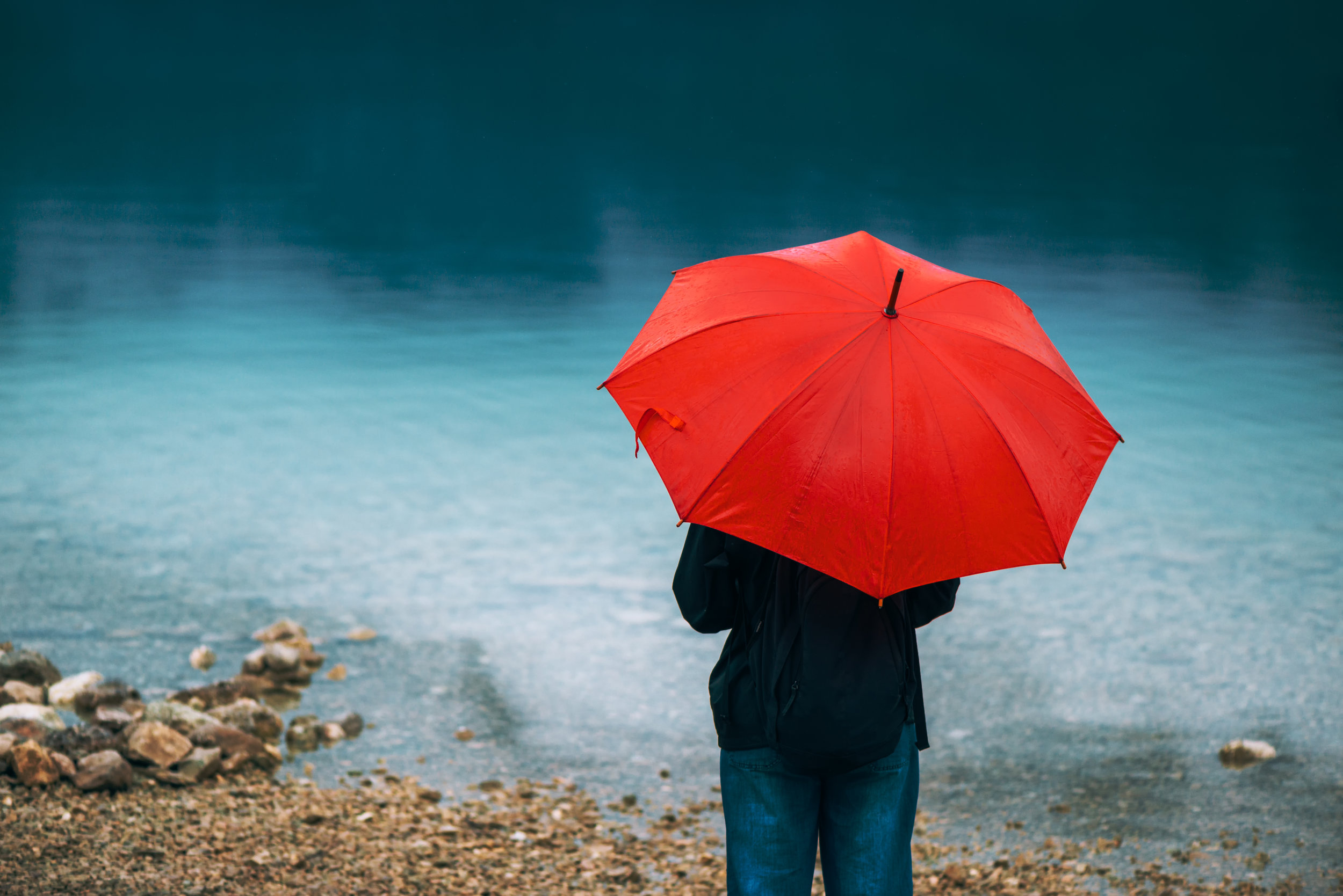 woman-with-red-umbrella-contemplates-on-rain-PJFZ6TW.jpg