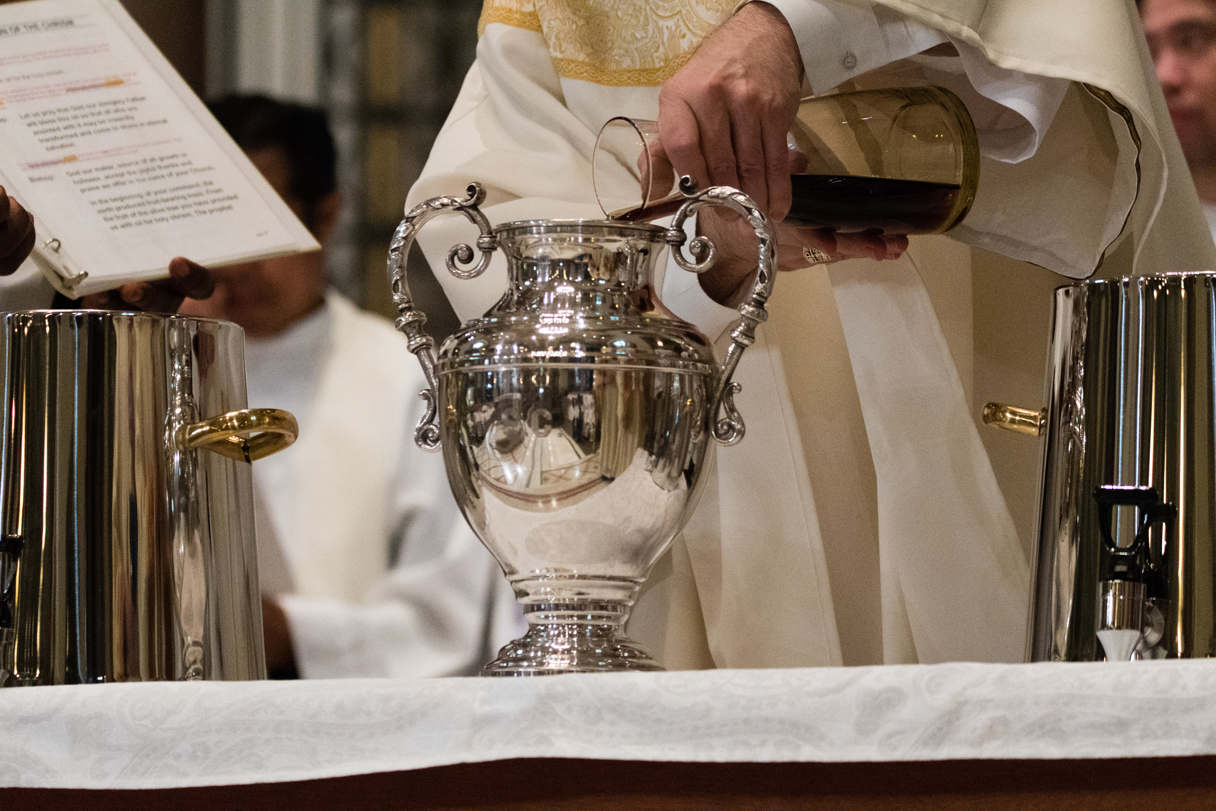 The Bishop pours and mixes the perfume in the oil to make the Sacred Chrism.
