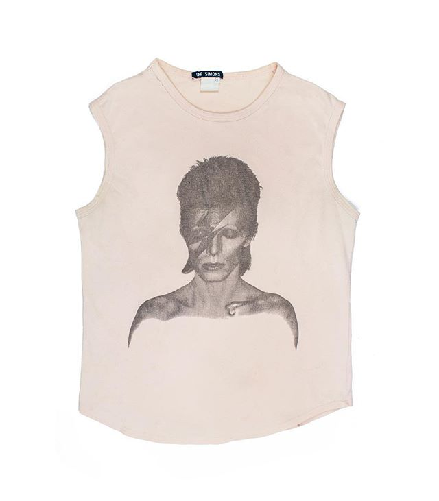"From the Middleman Personal Collection: Raf Simons SS1996 ""Aladdin Sane"" Tank. This top displays a monochrome rendering of the famous image from David Bowie's ""Aladdin Sane"" album cover. Released as a followup to ""The Rise and Fall of Ziggy Stardust and the Spiders from Mars"", the character was not an abandonment, but rather an evolution of its predecessor. Conceived while touring his previous album, Bowie described Aladdin Sane simply as ""Ziggy goes to America."" This shirt features a cropped and slim cut, with a stretchy, cotton-blend fit which is true to era of the shirts produced during Bowie's heyday. Not for sale. #middlemanstore"