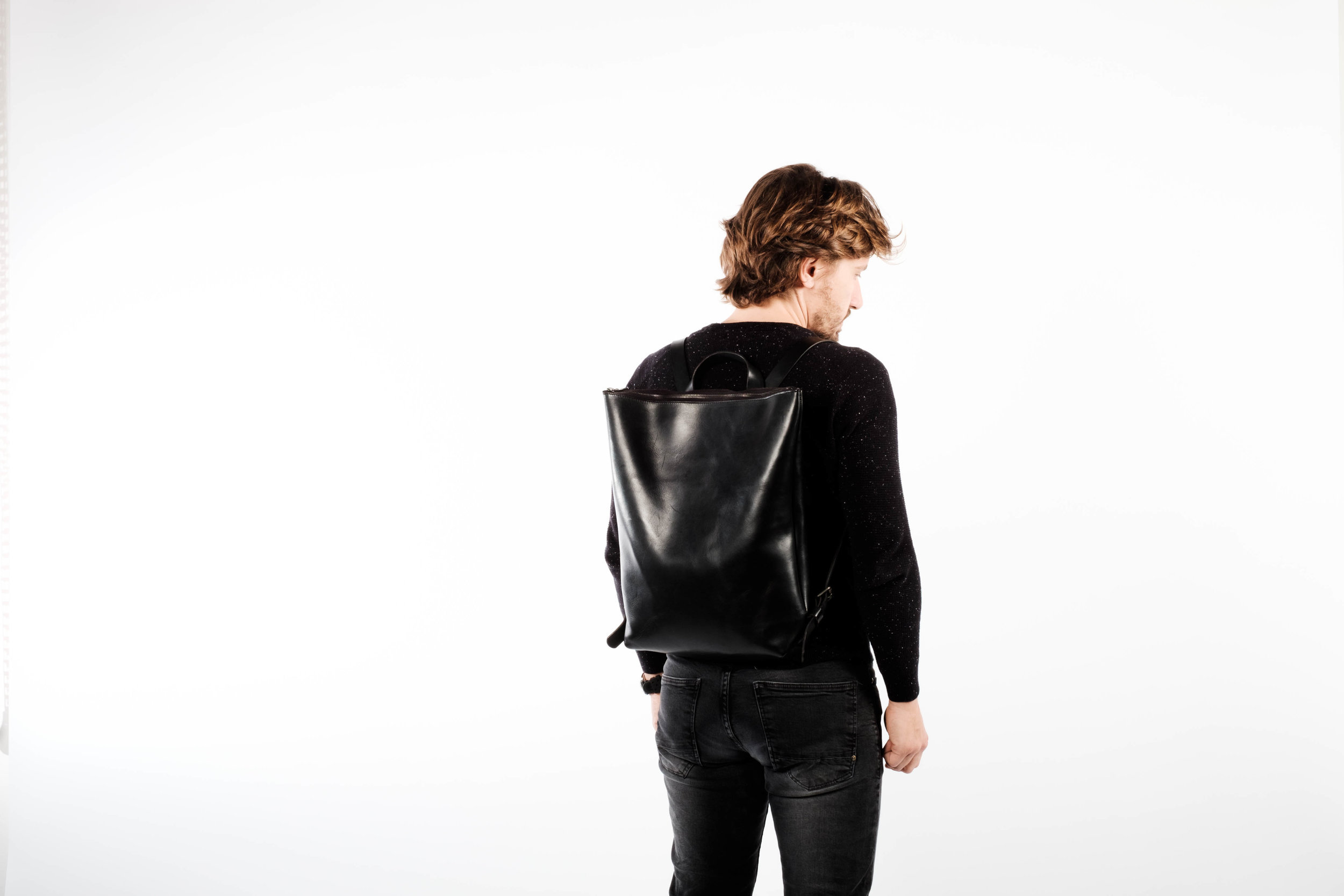 NO.02 is a minimalistic top-zip backpack with a top handle and an additional organizer on the inside of the bag. It is made of 1.8 mm smooth vegetable tanned leather with 3.5 mm thick shoulder straps.  It features nickle roller buckles on the side, swiss-made RIRI zip closure in gunmetal black and solid cast copper rivets that are hand forged to connect the straps to the bag. The cut edges of the leather are carefully rounded off and hand polished with beeswax to smooth finish.