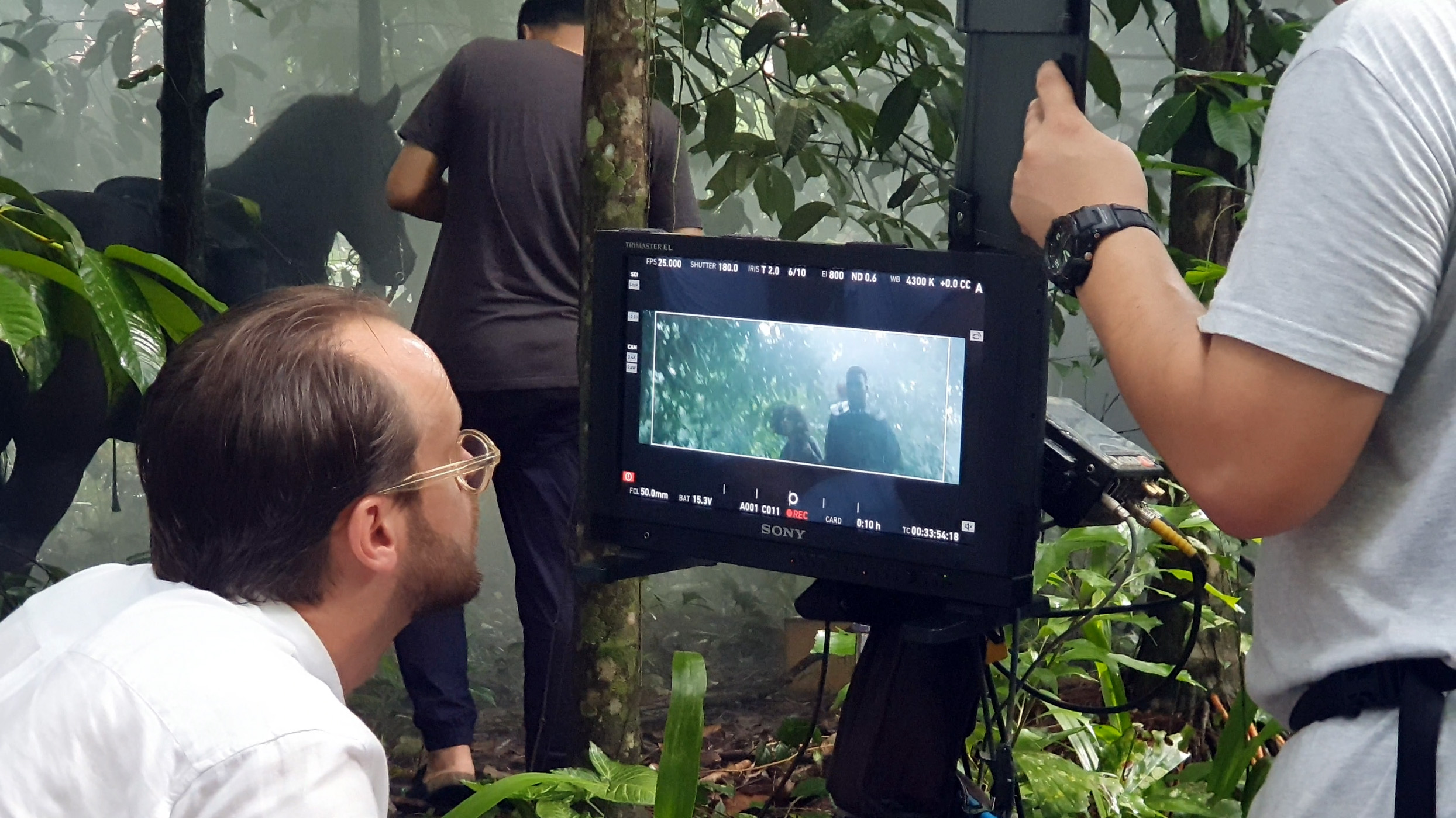 Director Filip is checking the framing in the jungle
