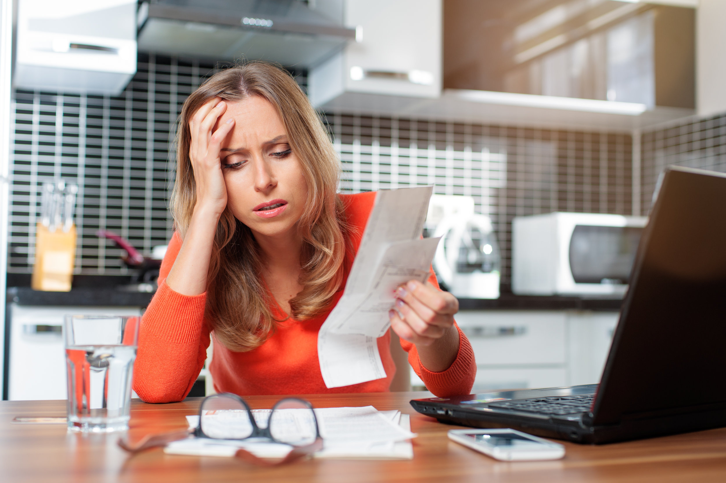 Woman sitting in kitchen stressed out about medical bills