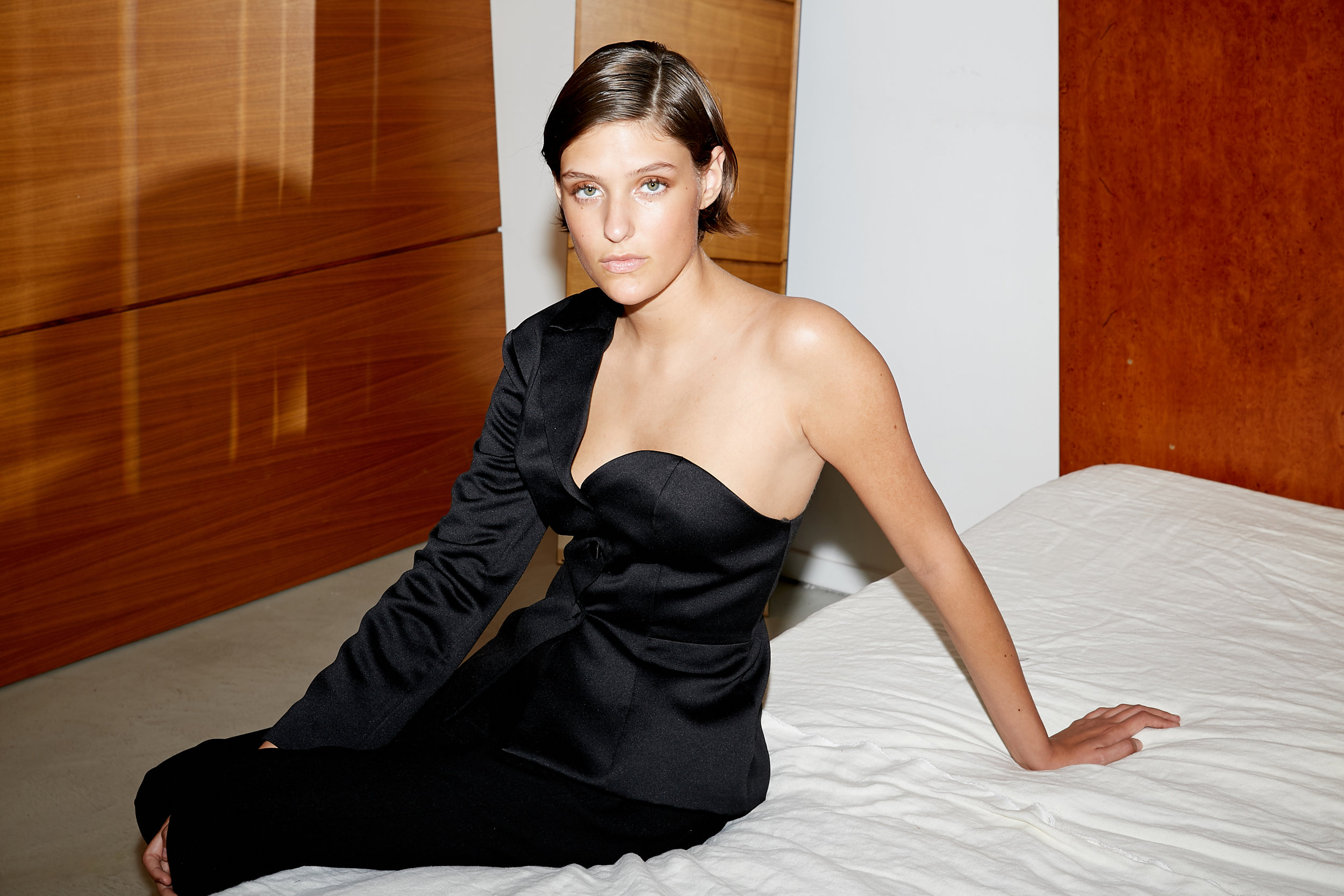 Model sits on bed in black satin half blazer half bustier one shoulder top with black tailored pants