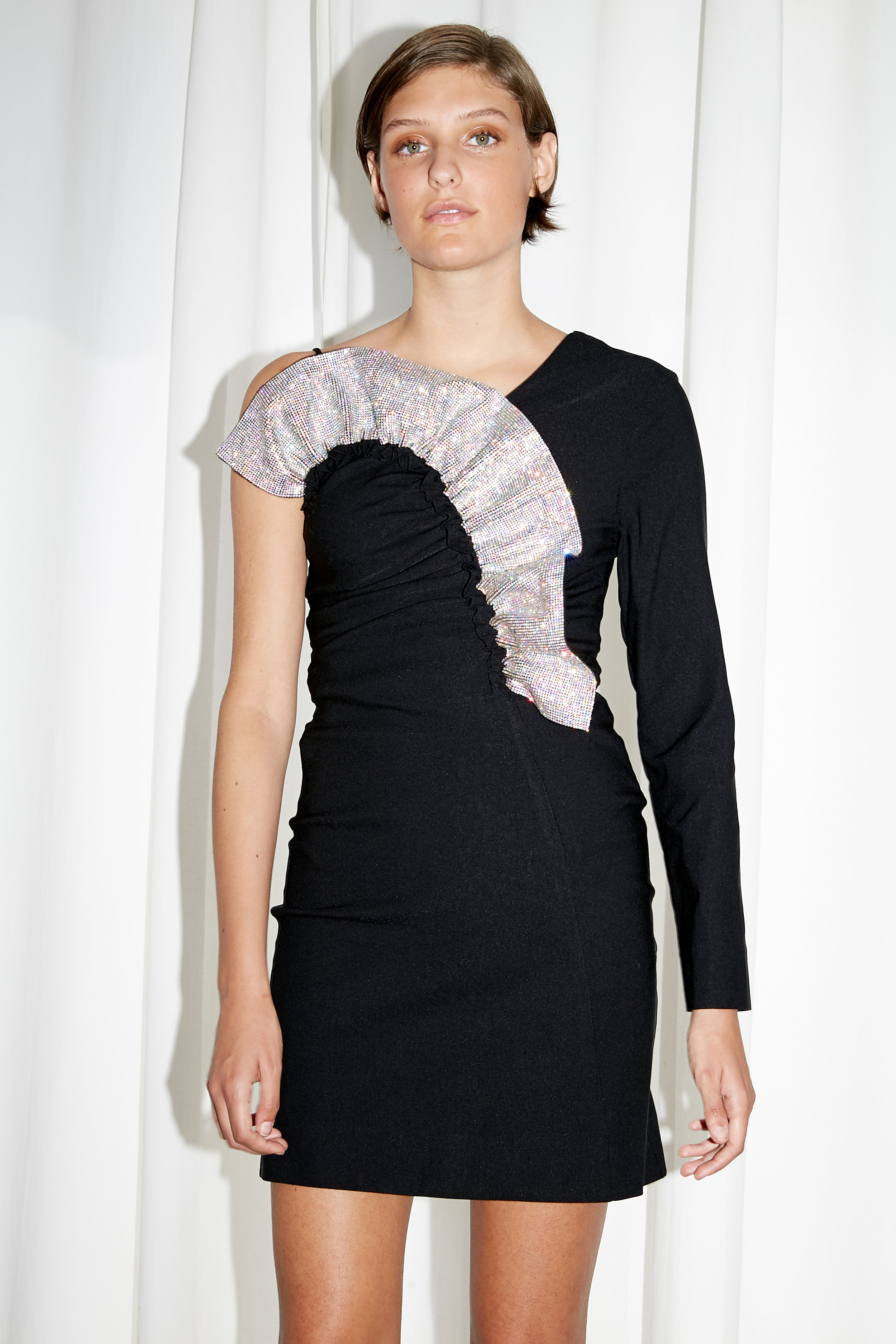 Model stands in short length one sleeve black dress with crystal ruffle neckline
