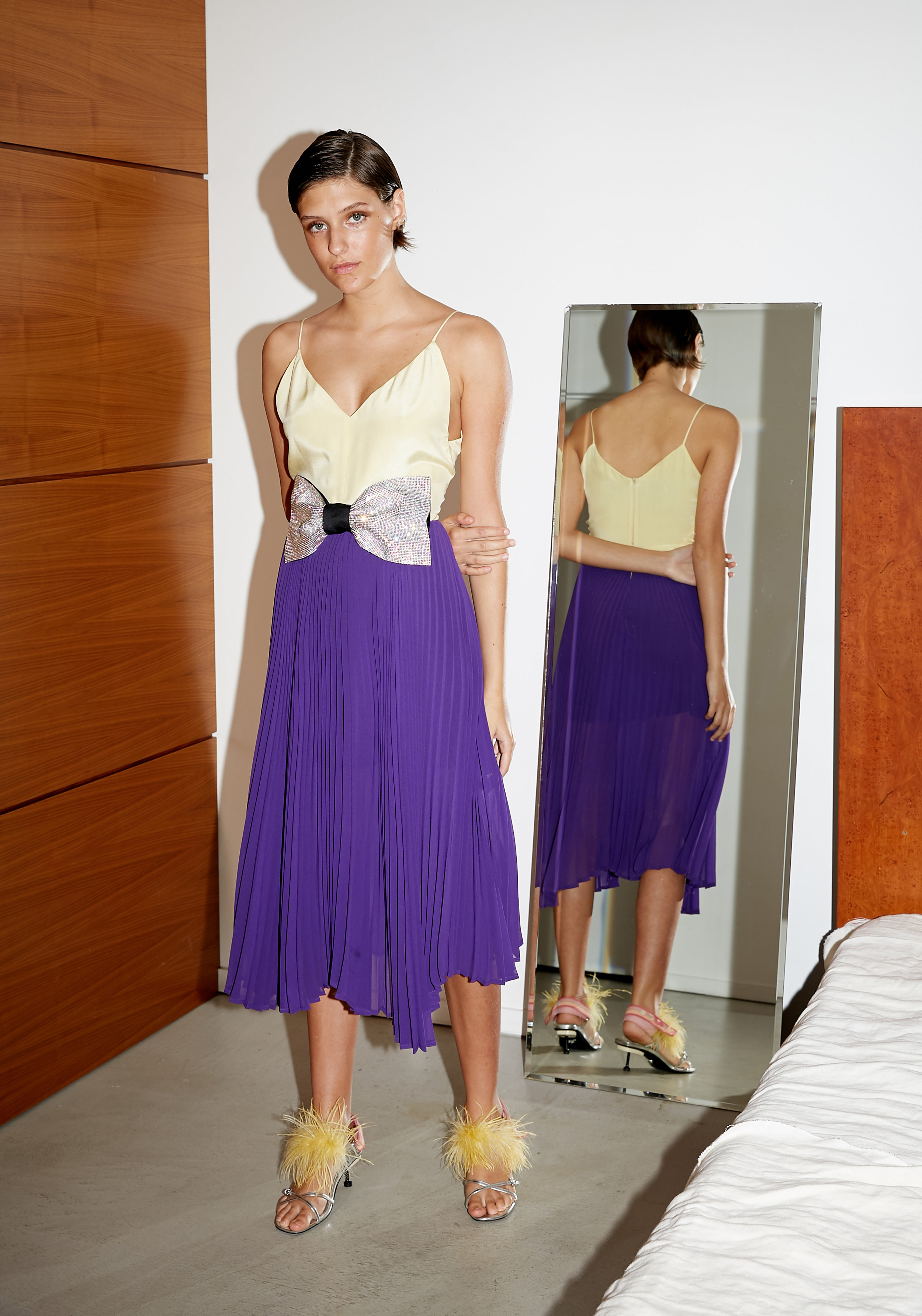 Model stands in color block dress with butter yellow cami on top and pleated skirt with crystal bow at it's waist
