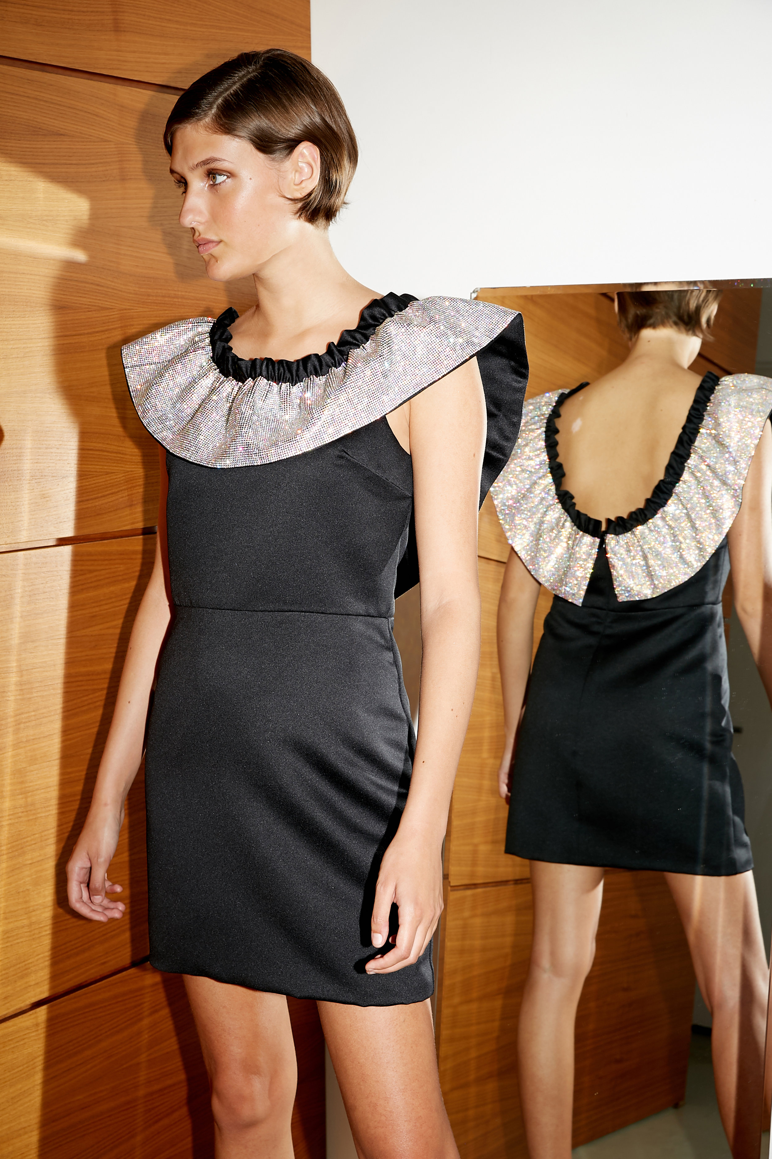 Model stands in black satin sheath mini dress with oversized crystal collar framing it's neckline
