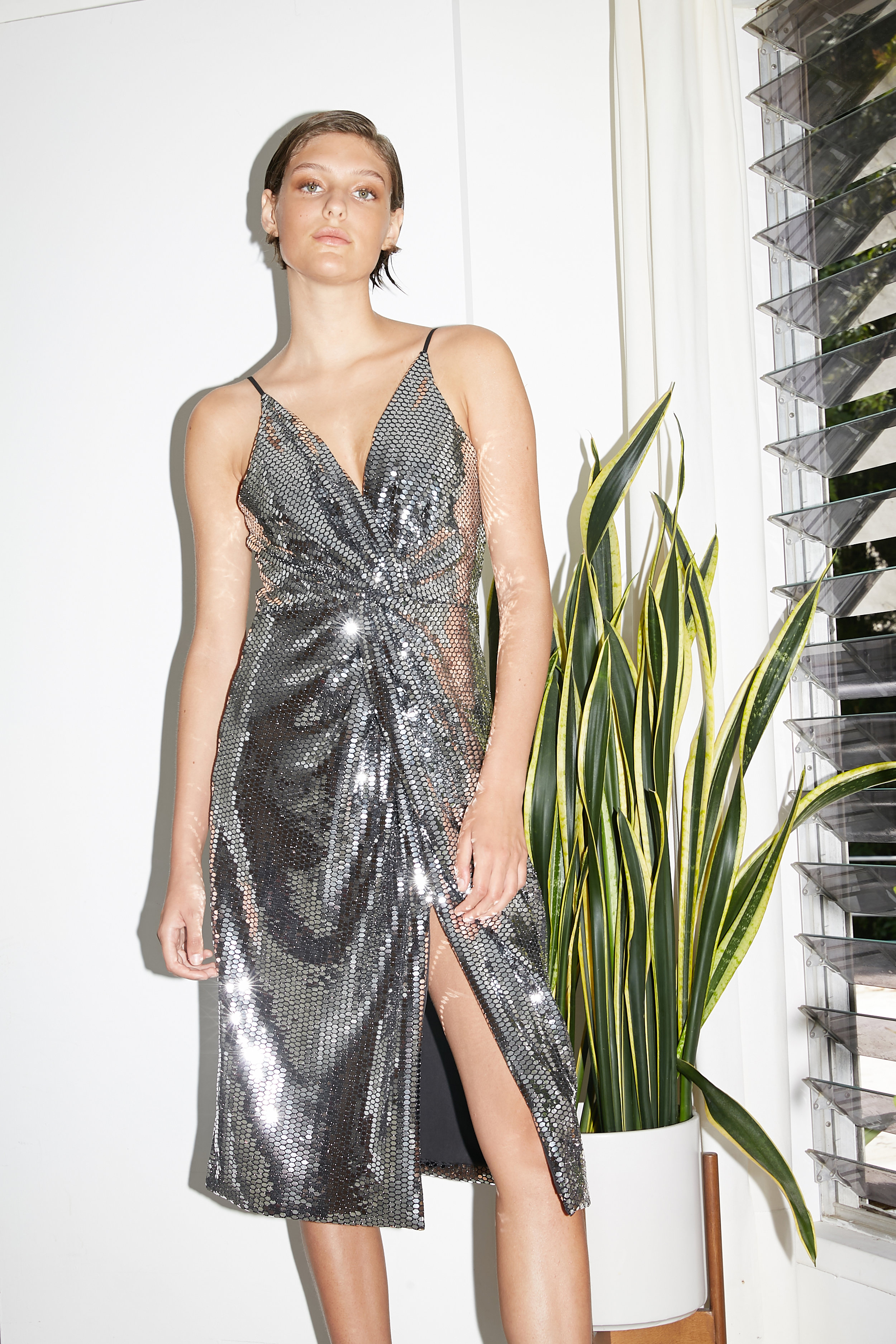 Model stands in knot front knee length mirrored wrap dress
