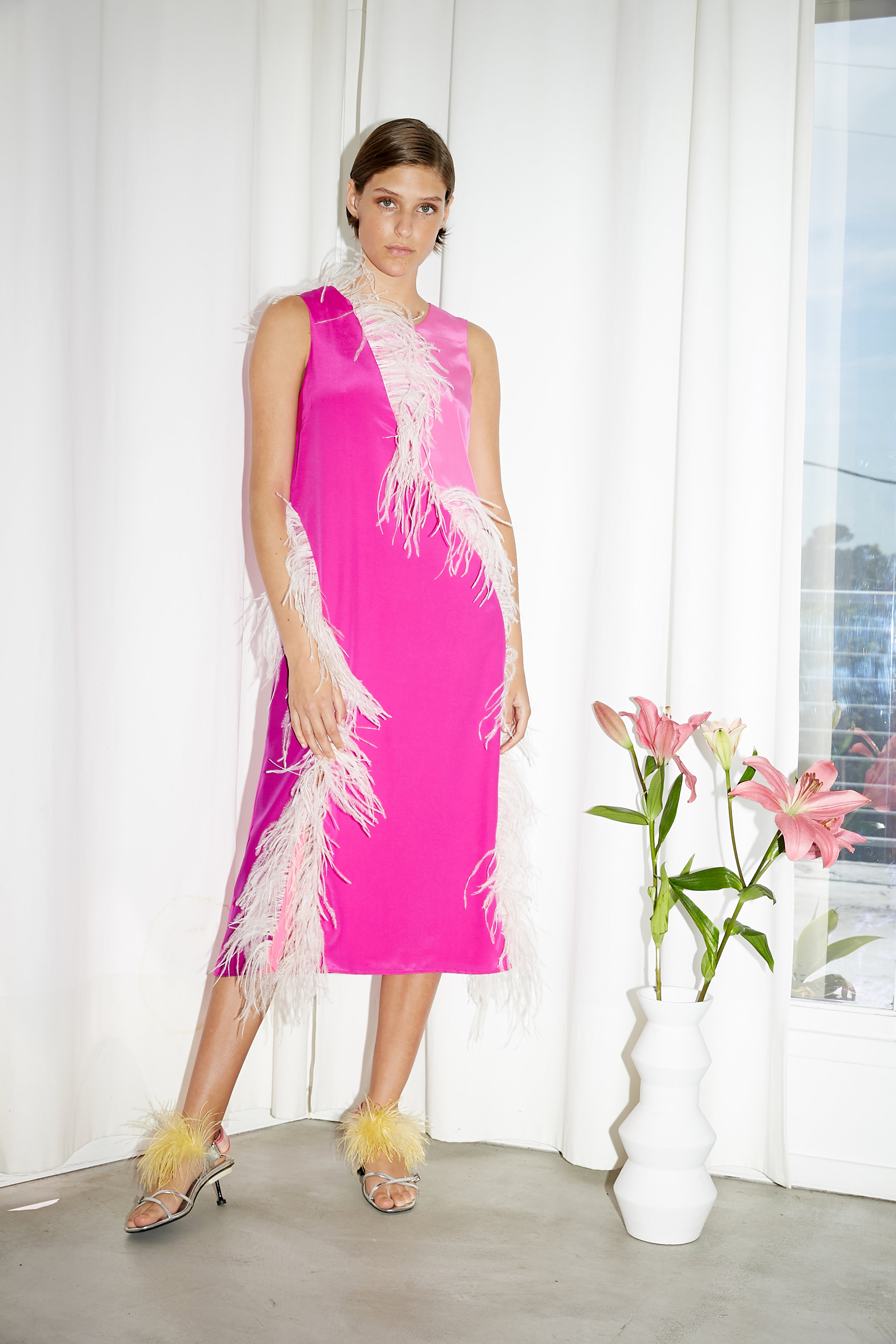 Model stands in pink color block dress with feather trim along seams