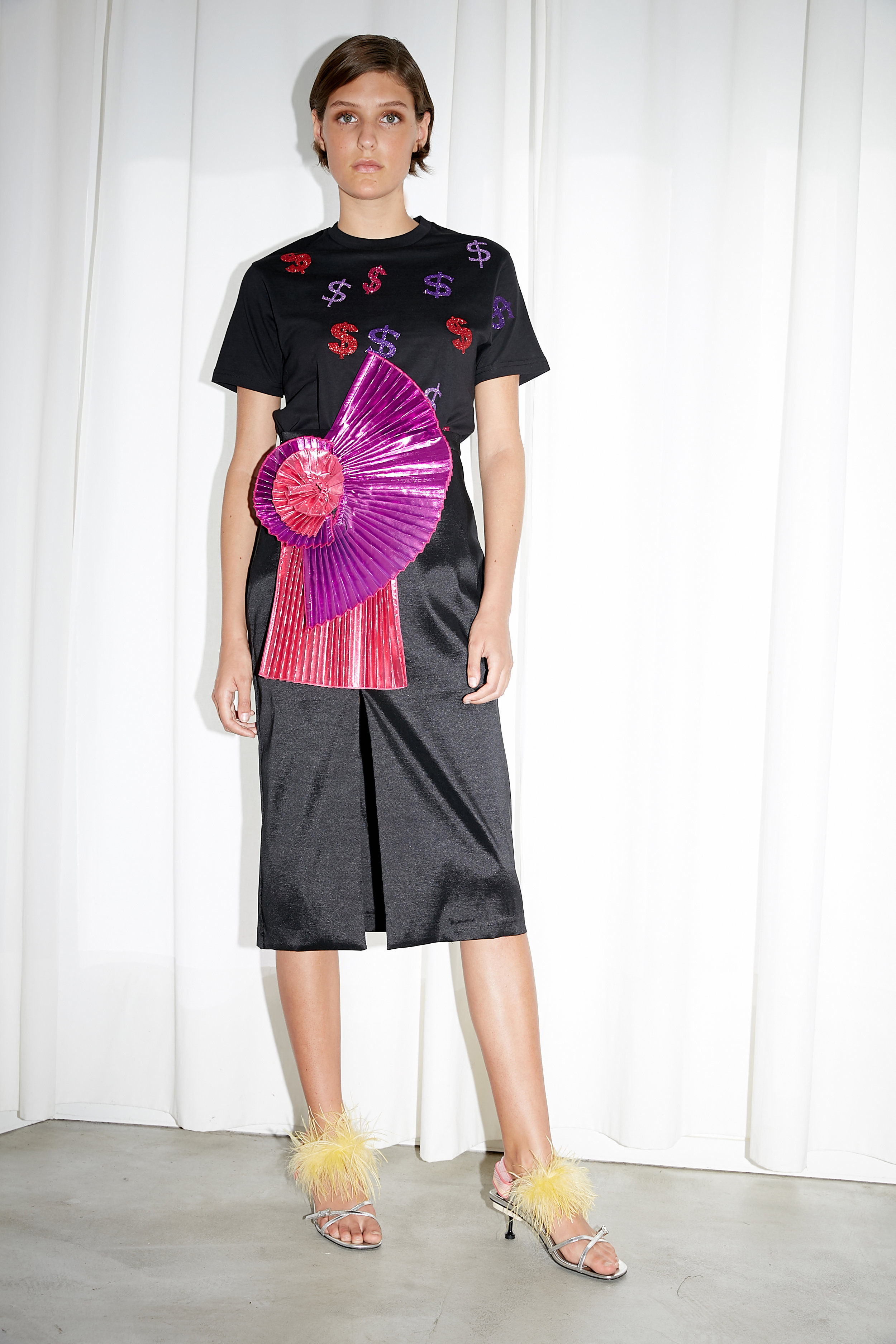 Model stands in black t-shirt printed with sparkling dollar signs in red, purple and pink and black satin skirt with oversized pleated fn detail at waist