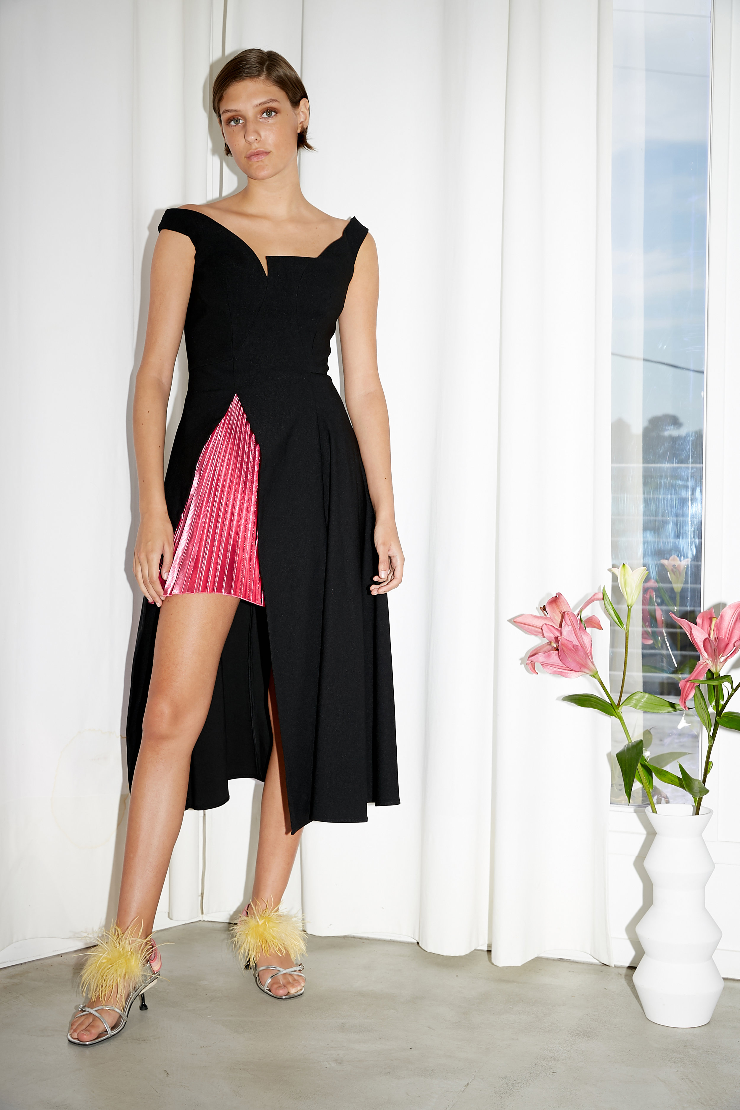 Model stands in black sleeveless dress with asymmetric neckline and high slit at hem revealing metallic pleated underskirt