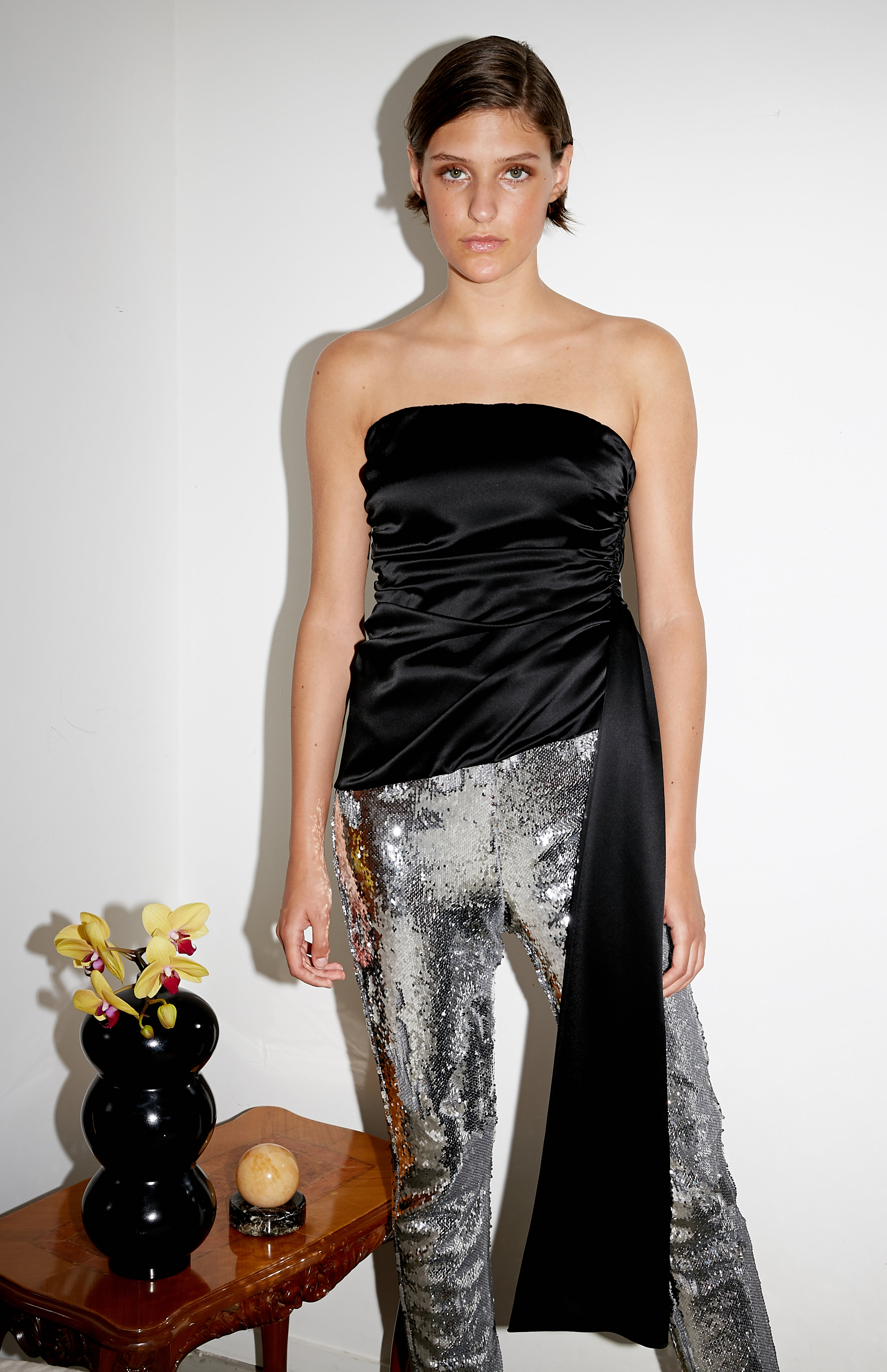 Model stands in black satin bandeau top with long sash detail and silver sequin pant
