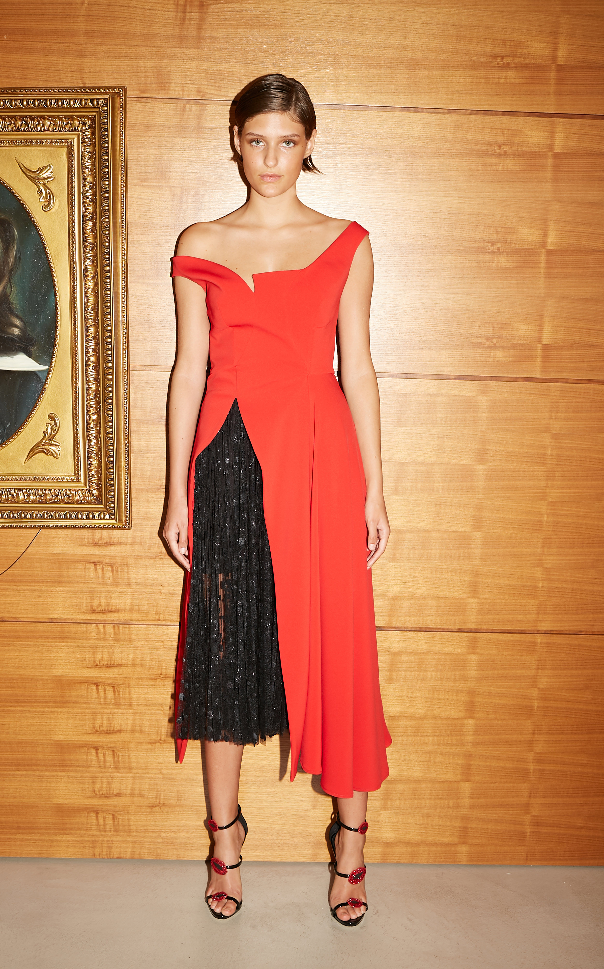 Model stands in sleeveless red tea length dress with asymmetric neckline and off centered slit revealing black sparkling tulle under skirt