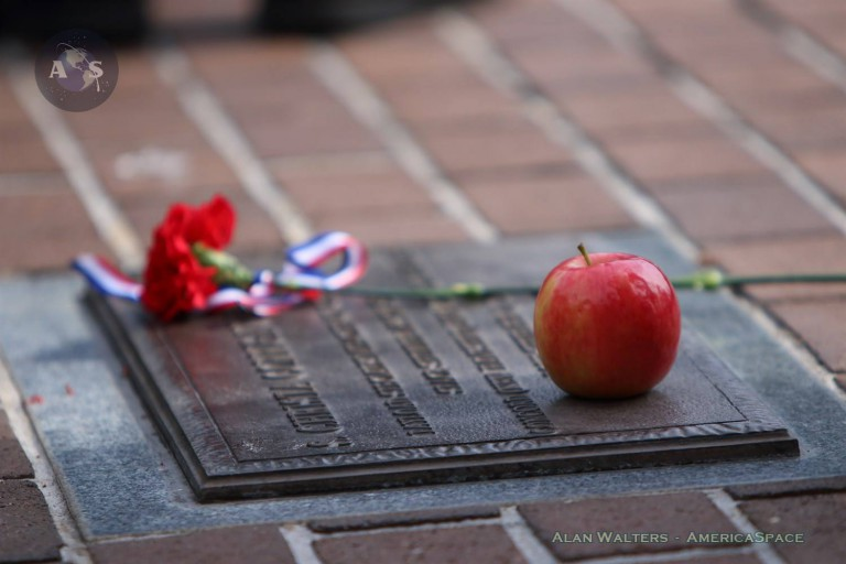 A single red carnation and, most touchingly, an apple decorate Christa McAuliffe's plaque at Titusville's Sand Point Park Saturday morning. McAuliffe was the first Teacher in Space, but perished aboard Challenger on Jan. 28, 1986. Photo Credit: Alan Walters / AmericaSpace