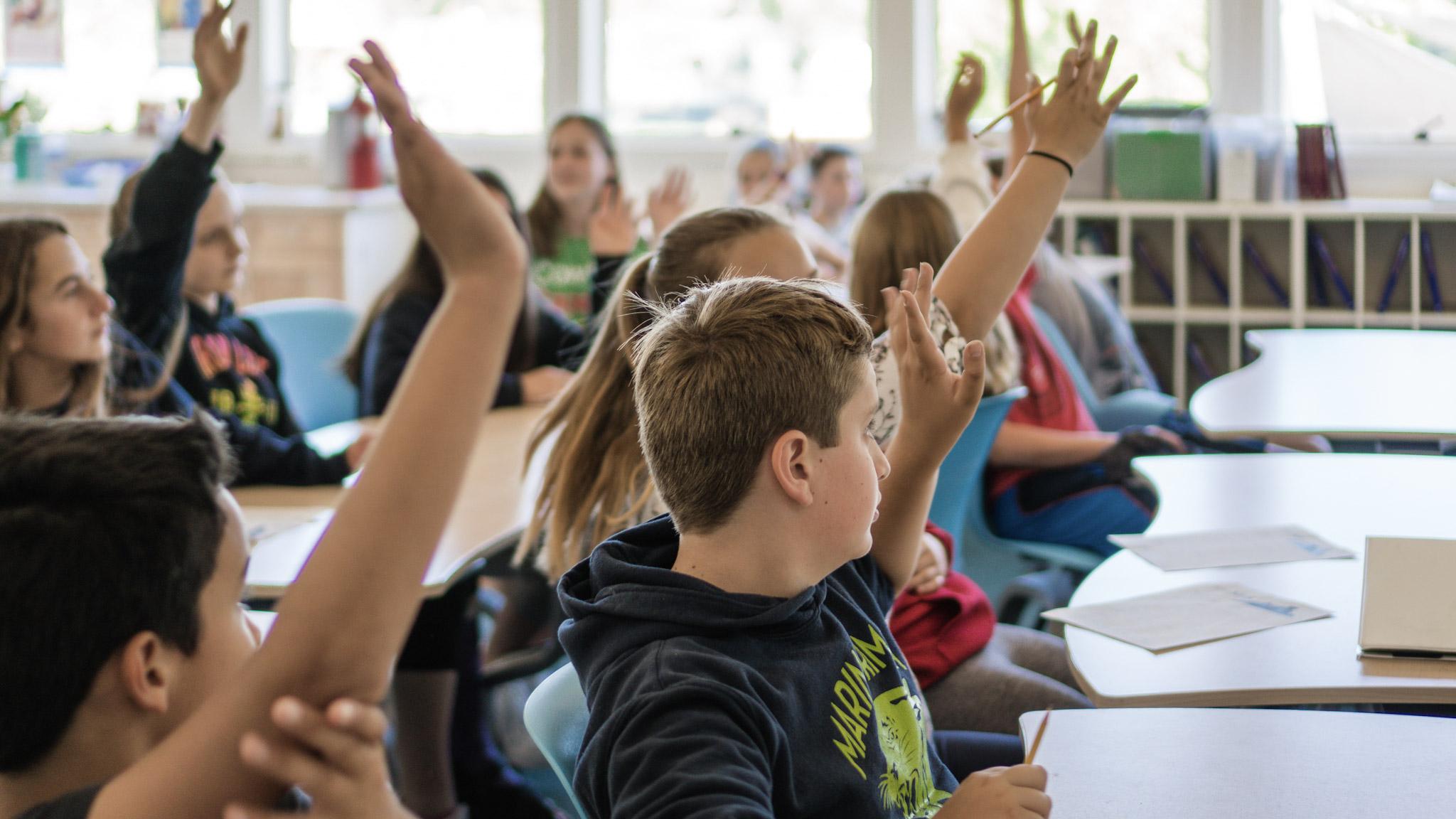 kids raising their hand in classroom.jpg