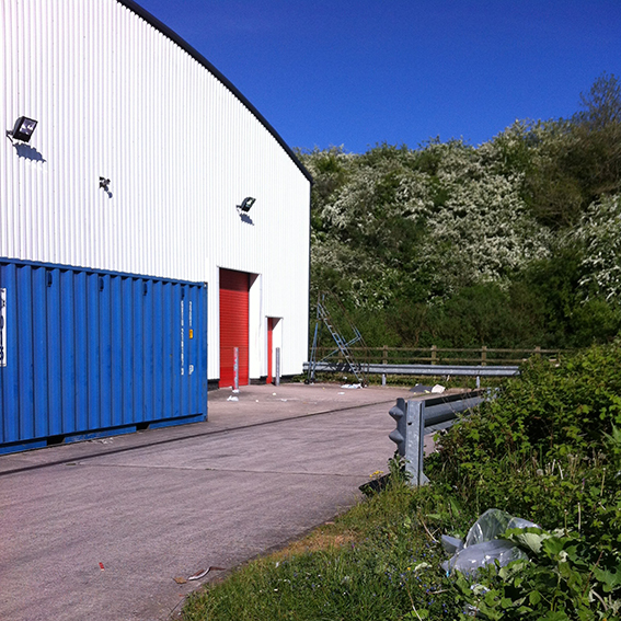 Storage units at the back of B&Q. The railway line is at the top of the bank of foliage.