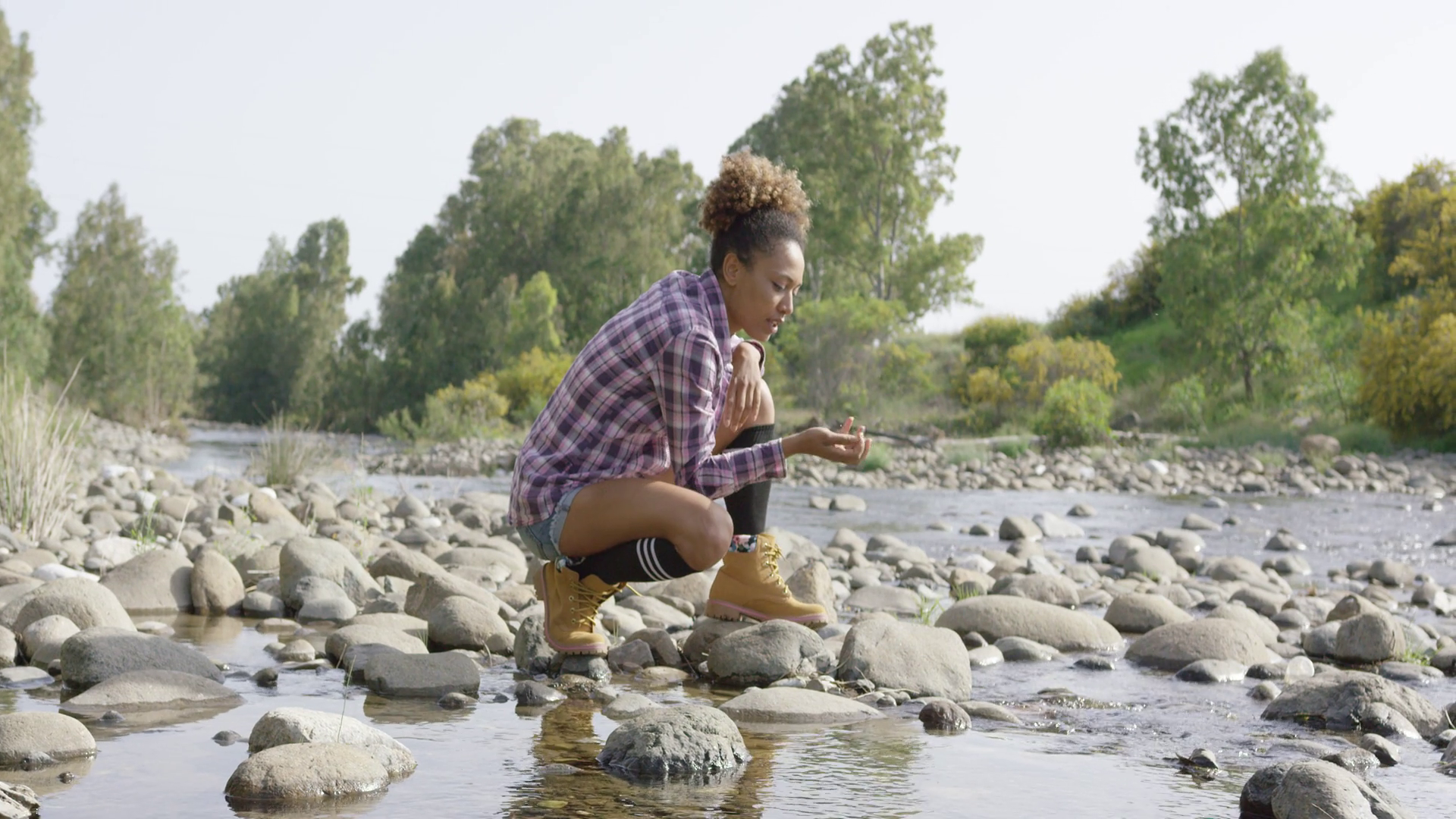 videoblocks-young-woman-sitting-among-creek-on-rock-and-throwing-small-stones-in-water-with-trees-on-background_h2xowpersg_thumbnail-full01.png