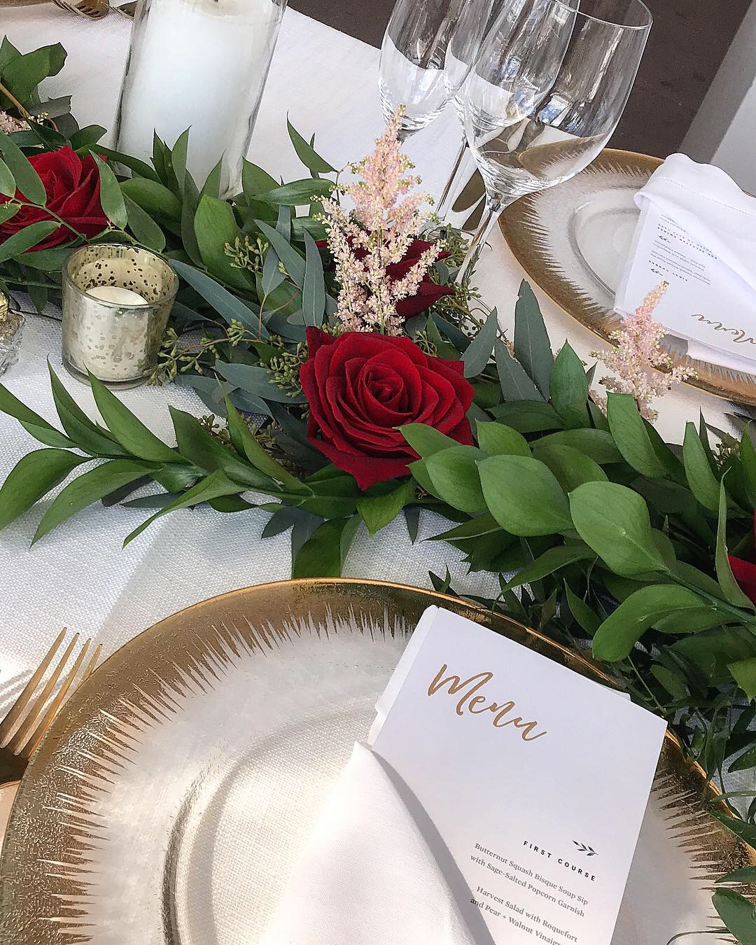 Long centerpiece made with red roses and greenery