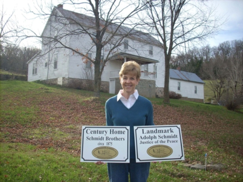 Gloria Ridder standing in front of The SchmidtThird Creek Farm, Inc. home, recently designated a Gasconade County Historical Society Century Home. This home was built by the Schmidt brothers, circa 1875.
