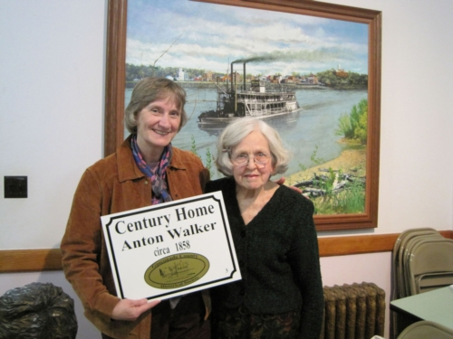 Anna Rademacher presents Rita Thomas with her Century Home Sign at a recent GCHS membership meeting held in the Gasconade County Court House in Hermann, Missouri.
