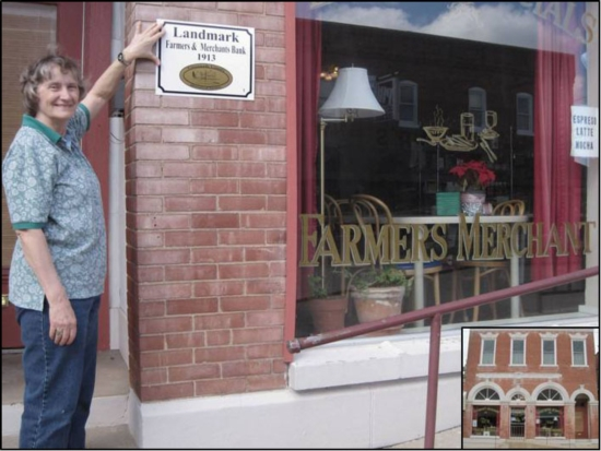 Anna Rademacher places the first Century Landmark sign on the exterior of her resturant  housed in the Farmer's Merchant Bank Building (inset) located on Owensville's Main Street.