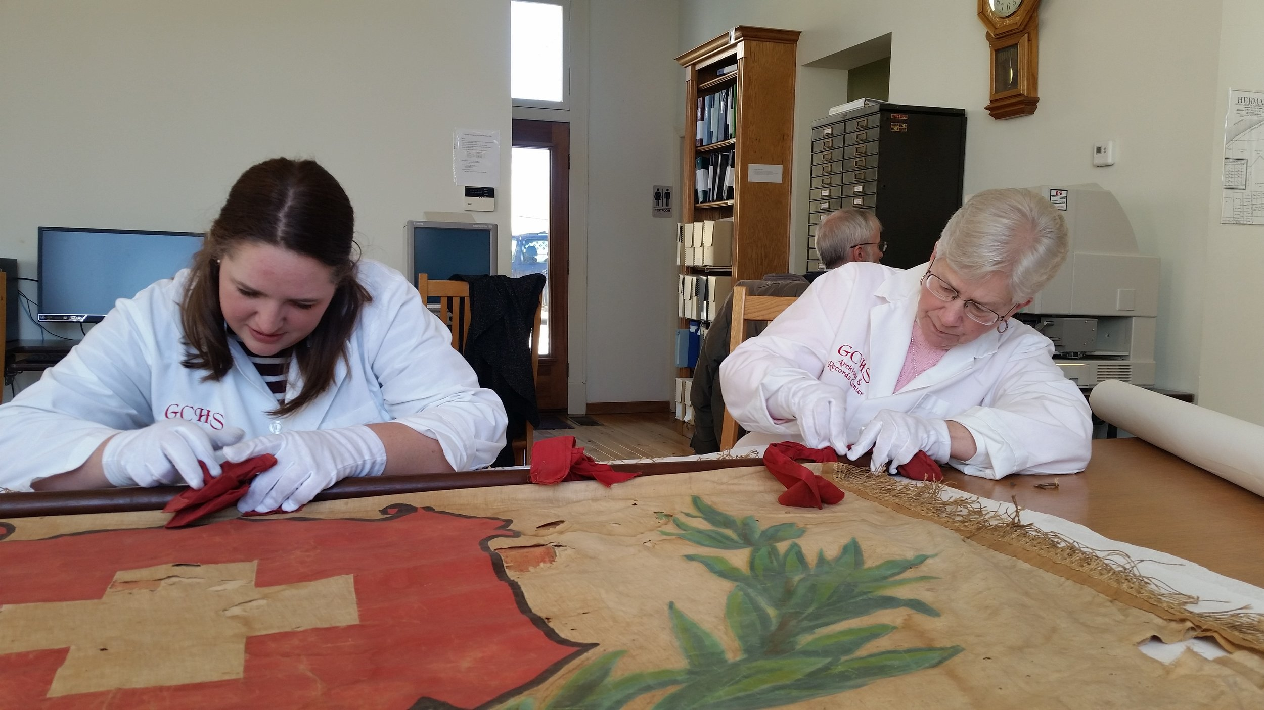 Kristy Goss (left) and Lois Kruse work on the old Swiss Society Helvetia banner that was recently discovered at the Courthouse in Hermann