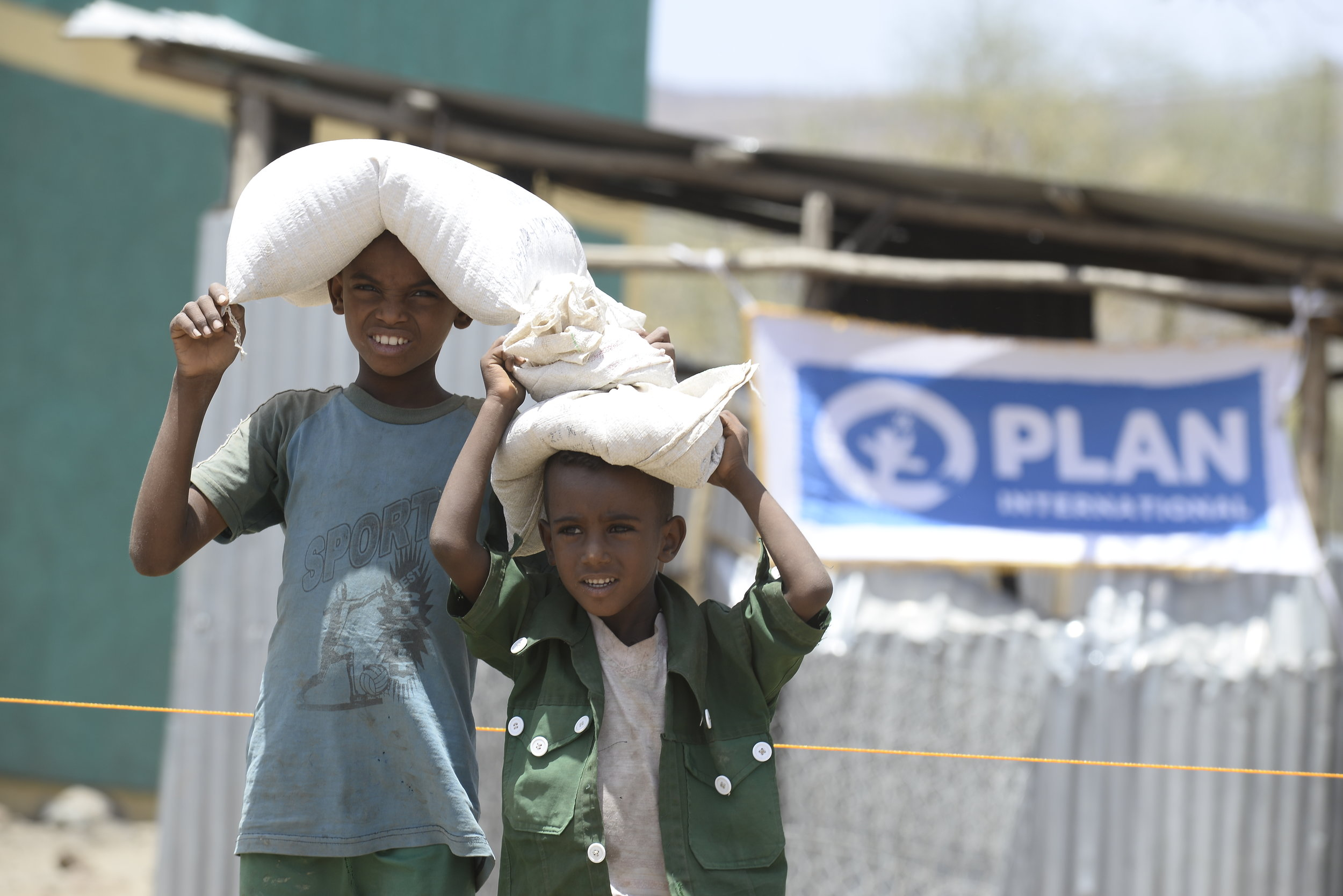 Children take home supplementary food from a health station in Amhara Region, Ethiopia. June 2016 ©Plan International/Michael Tewelde