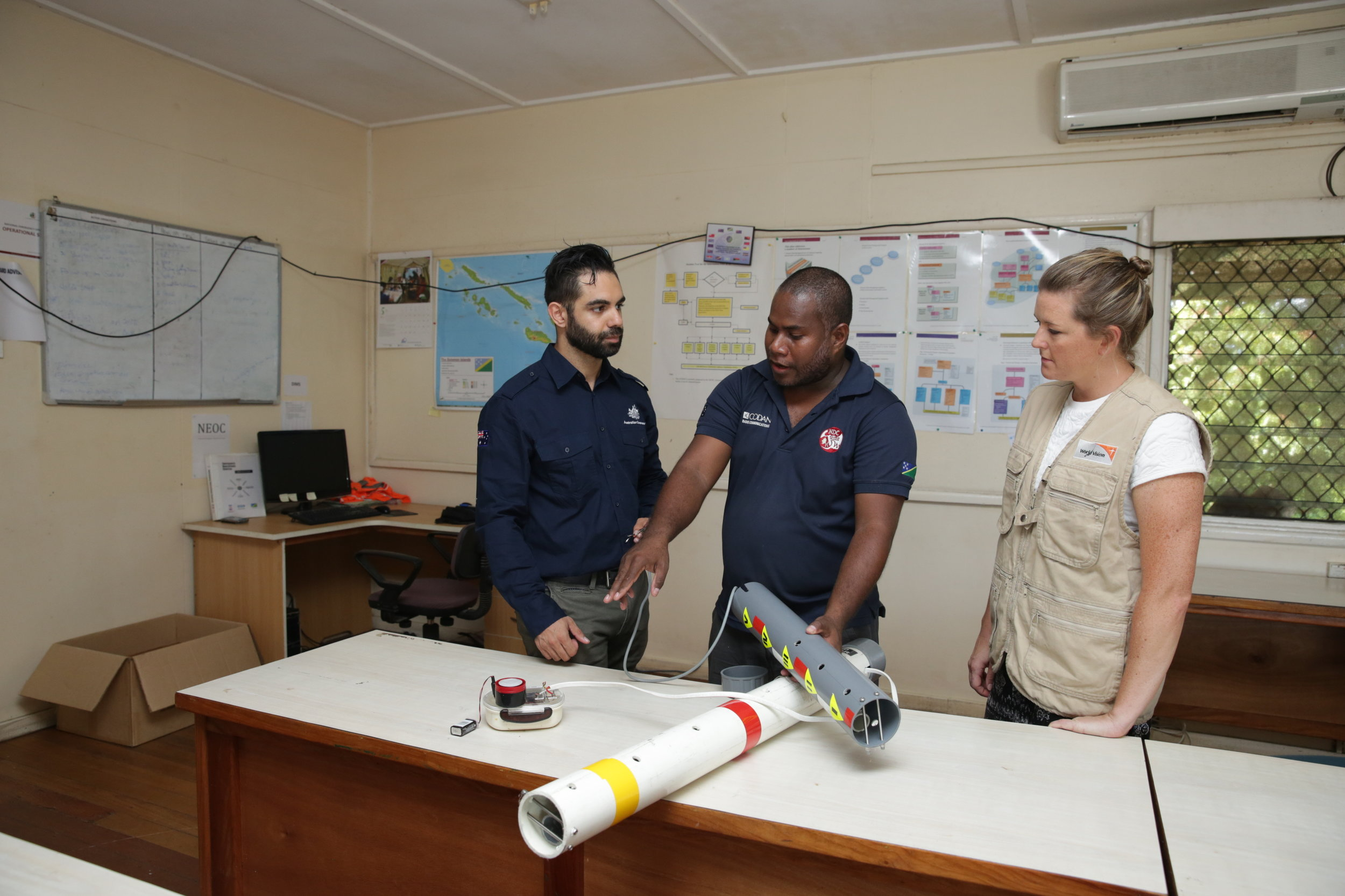 Photo caption: George Baragamu, Deputy Director of the National Disaster Management Office (NDMO), discusses flood gauges with representatives from the Australian Government and World Vision. Photo credit: ©World Vision Australia.