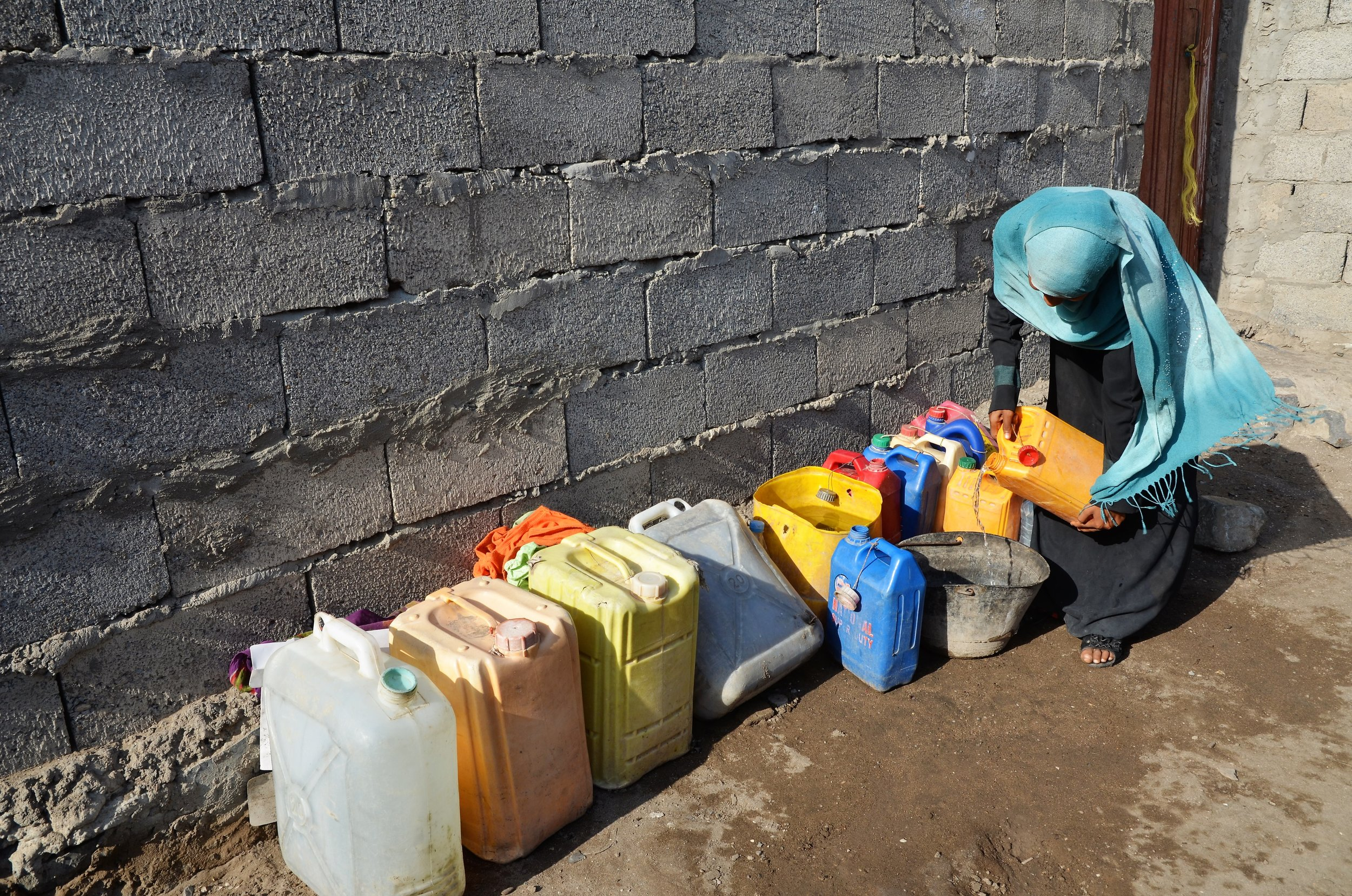 Photo caption: Sarah empties the water from bottles. Photo credit: Save the Children.