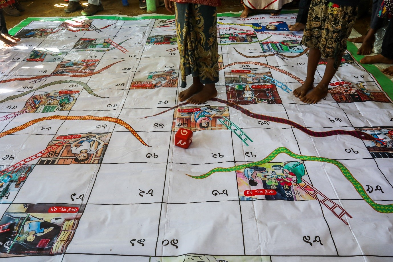 Photo caption: Children play a snakes and ladders game to learn about safe water, sanitation and hygiene (WASH) facilities and practices. Photo credit: Salahuddin Ahmed/Oxfam Australia. Date: January 2018.
