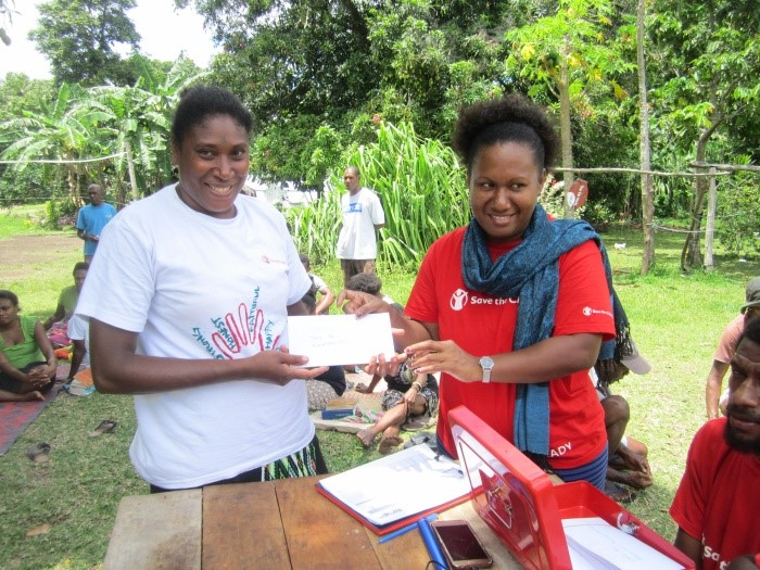Above: An Ambae resident who evacuate to nearby Maewo island to escape intense ash that continues to be spilled from the Monaro volcano on Ambae receives cash through the Cash for Work program.