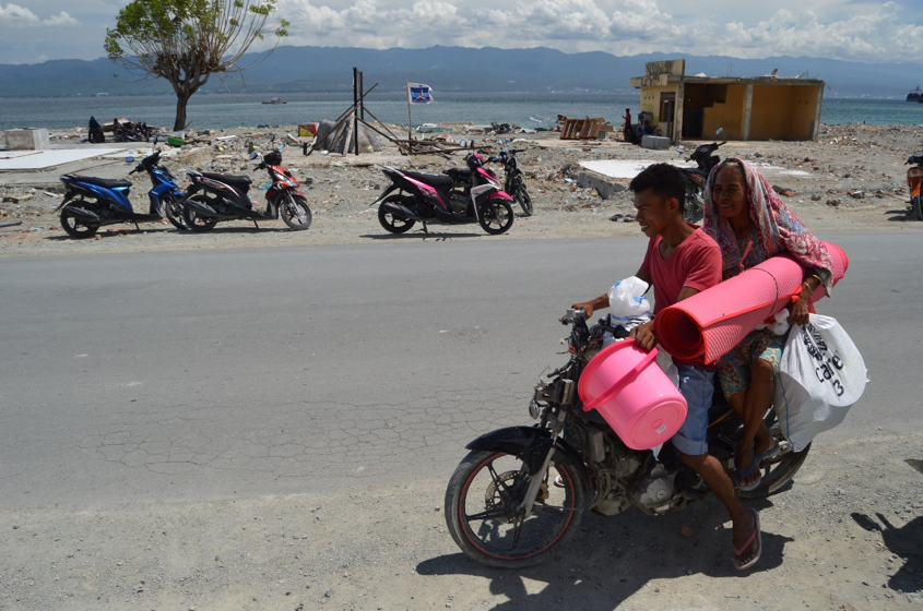 Above: A boy in Loli Saluran village, Donggala, Central Sulawesi, helps his parents to bring home shelter and hygiene kits which consist of tarpaulins, a mattress, sanitary napkins for women and girls, and soap (enough for one household's needs for one month).